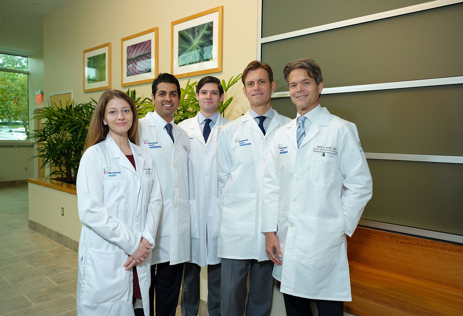 A group of one female doctor and four male doctors in white Northwell lab coats smile at the camera.