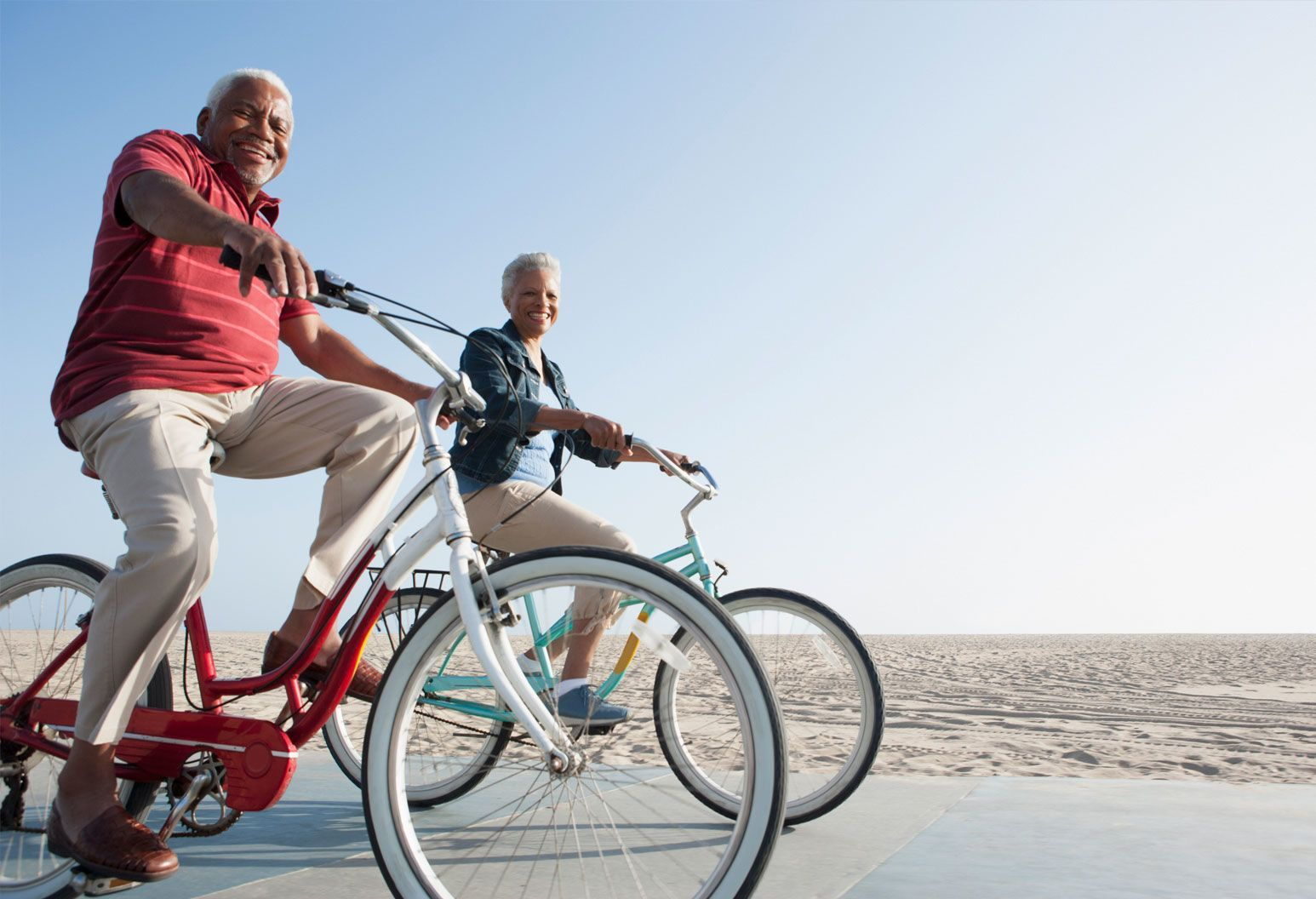 An elderly man and woman ride bikes on the sidewalk at the beach. They are both smiling and looking at the camera. It's a clear day with a blue sky and the sun is shining.