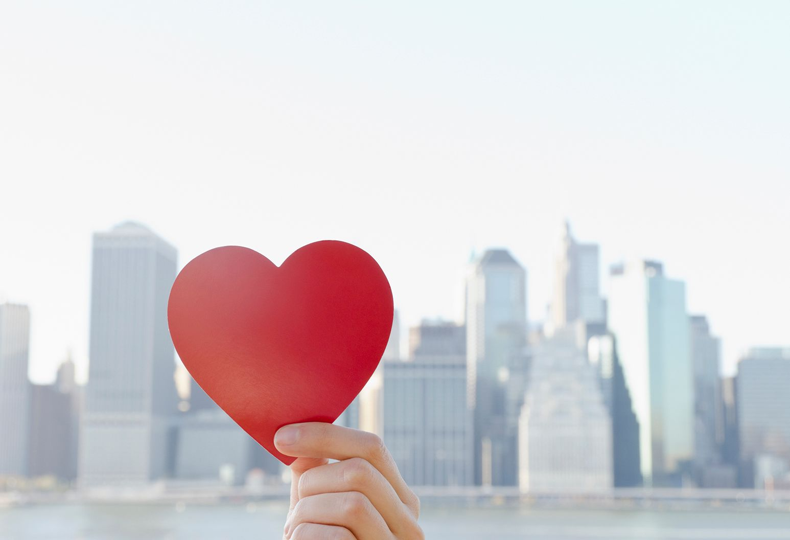 Hand holding a paper cut out of a heart, city skyline in the background