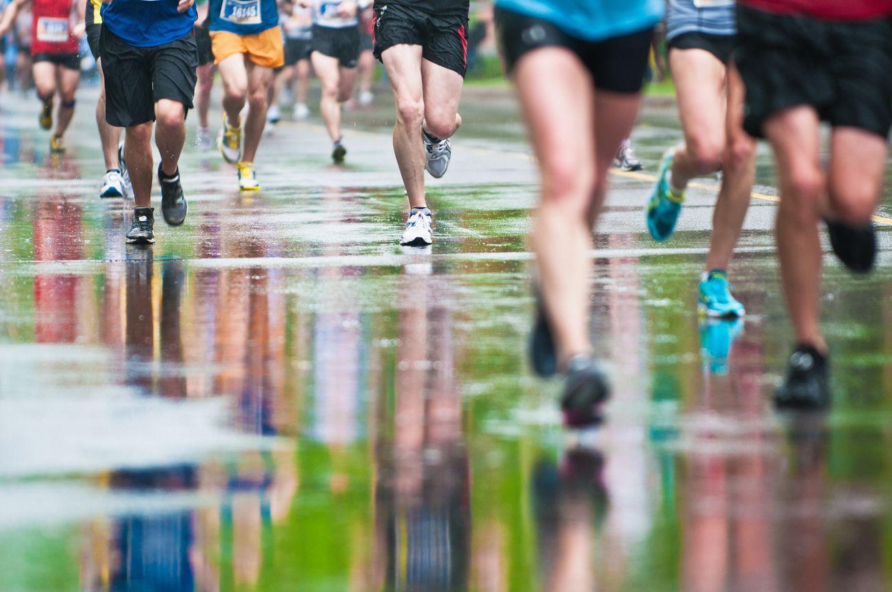 Legs running on wet pavement