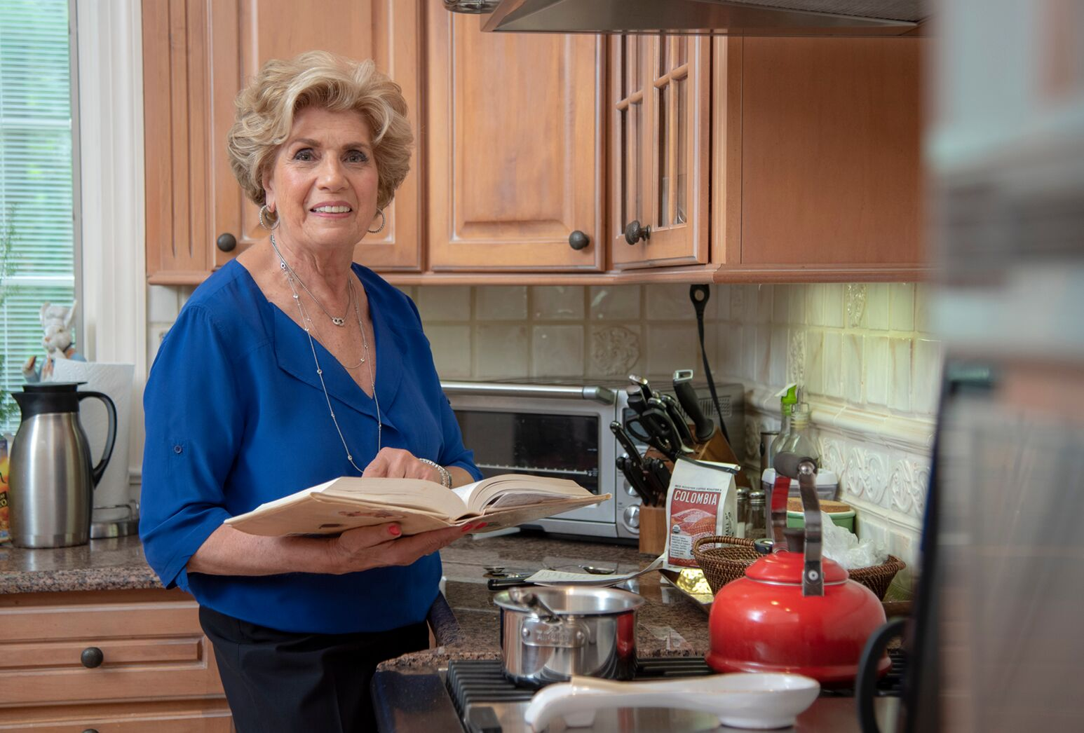 Woman in her 70s in kitchen with cookbook preparing a meal.