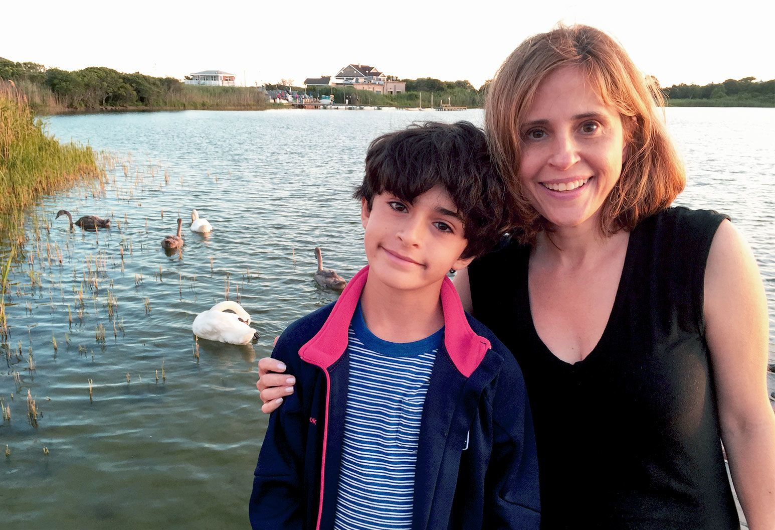 a young boy with curly black hair, a striped shirt displays a faint smile as he stands in front of a lake with an older woman with her hand on his shoulder. She has shoulder length auburn hair, and wears a black top. In the lake are geese treading in the