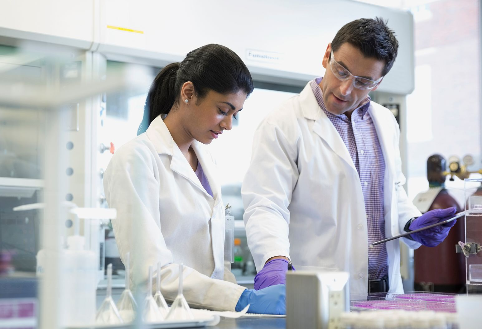 Male and female medical researchers in a lab working together to find a solution.