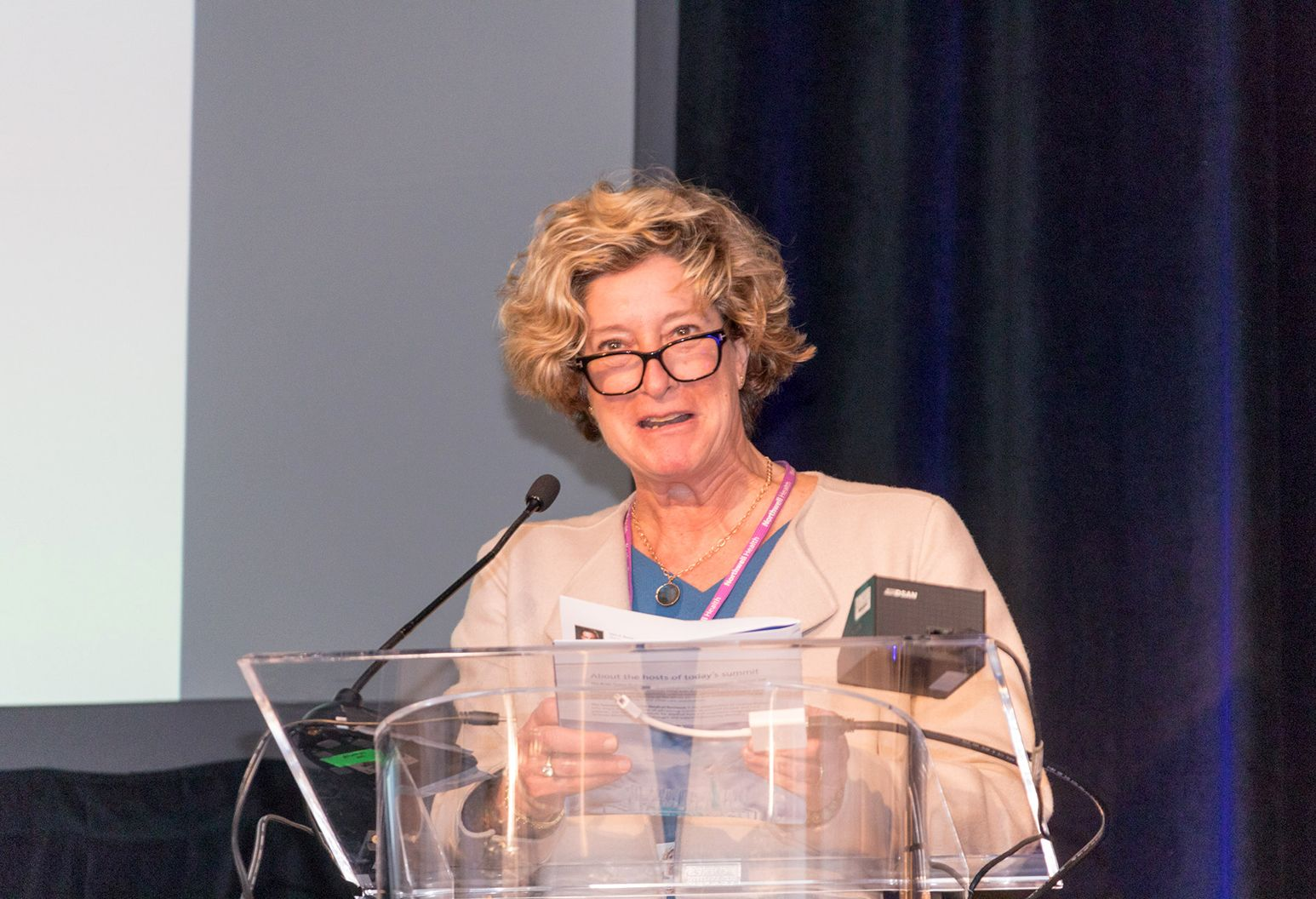 Middle aged woman stands behind a podium on stage at a conference