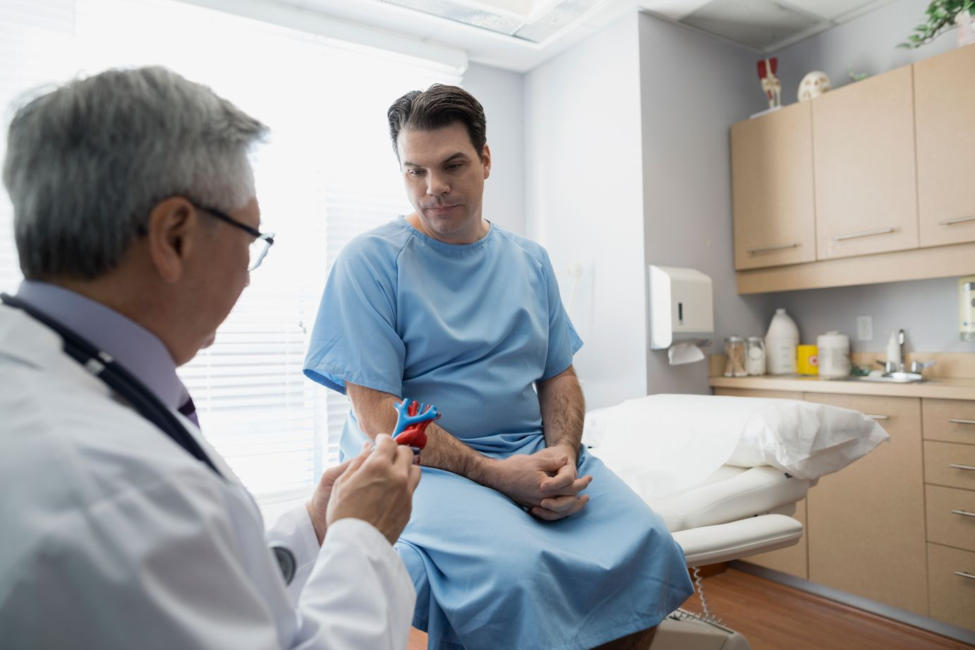 Middle aged male sits on examination table in blue hospital gown as male doctor in white lab coat shows him a model of the heart.