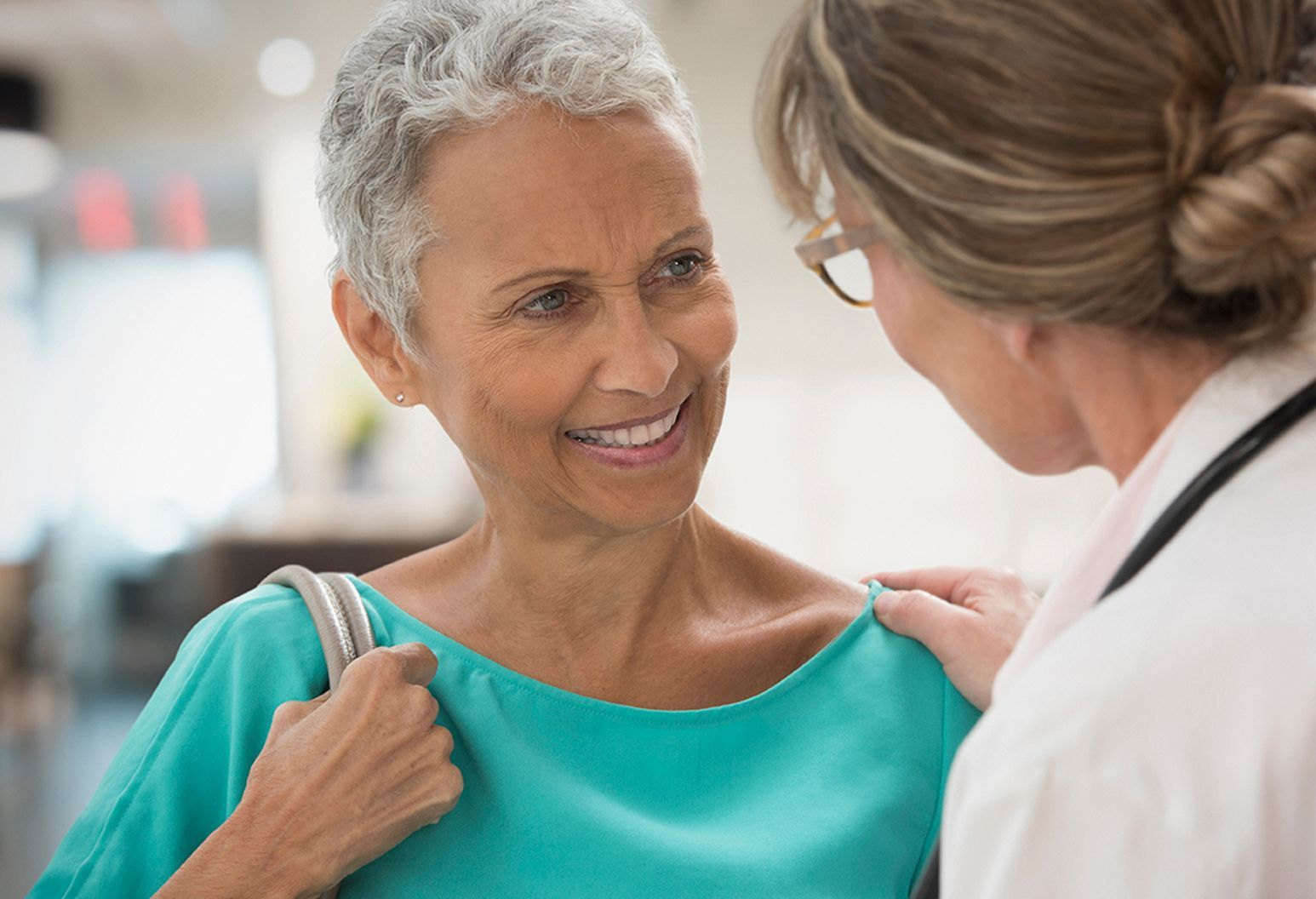 Older woman smiling as she talks to her female doctor