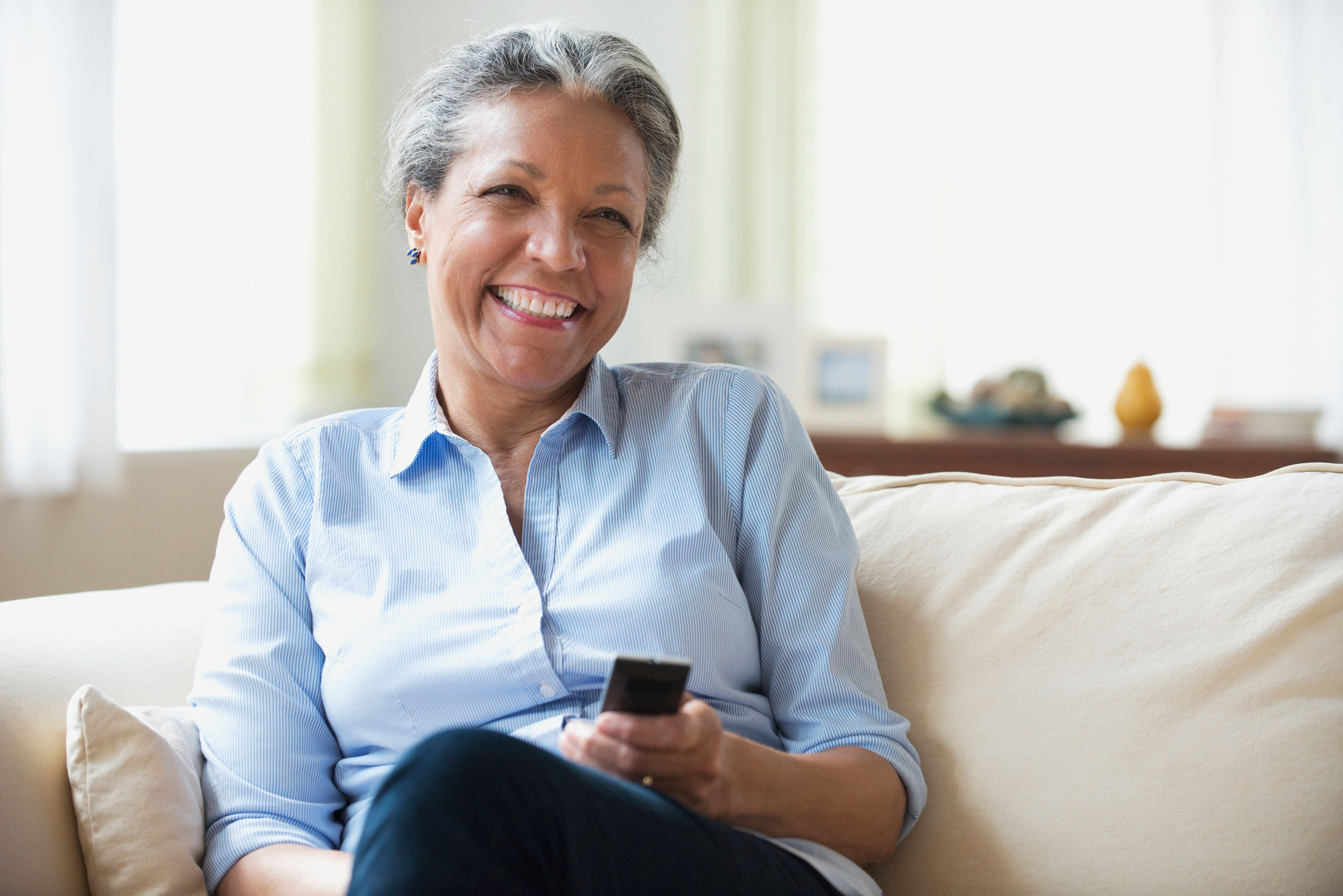 A woman holds a remote control and smiles