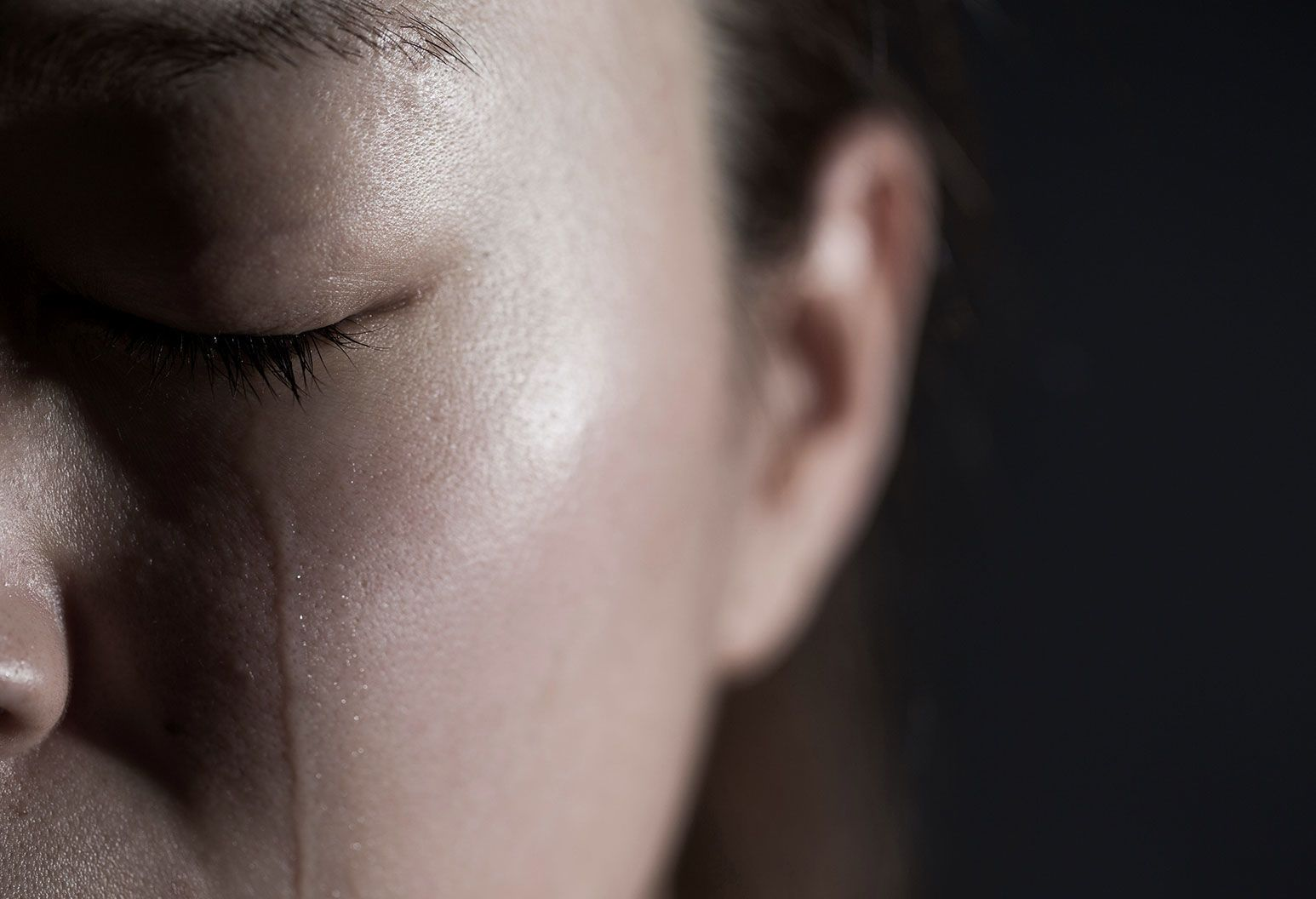 Close up of half a woman's face with her eyes closed and a tear trailing down her face. She is also in a dark room.
