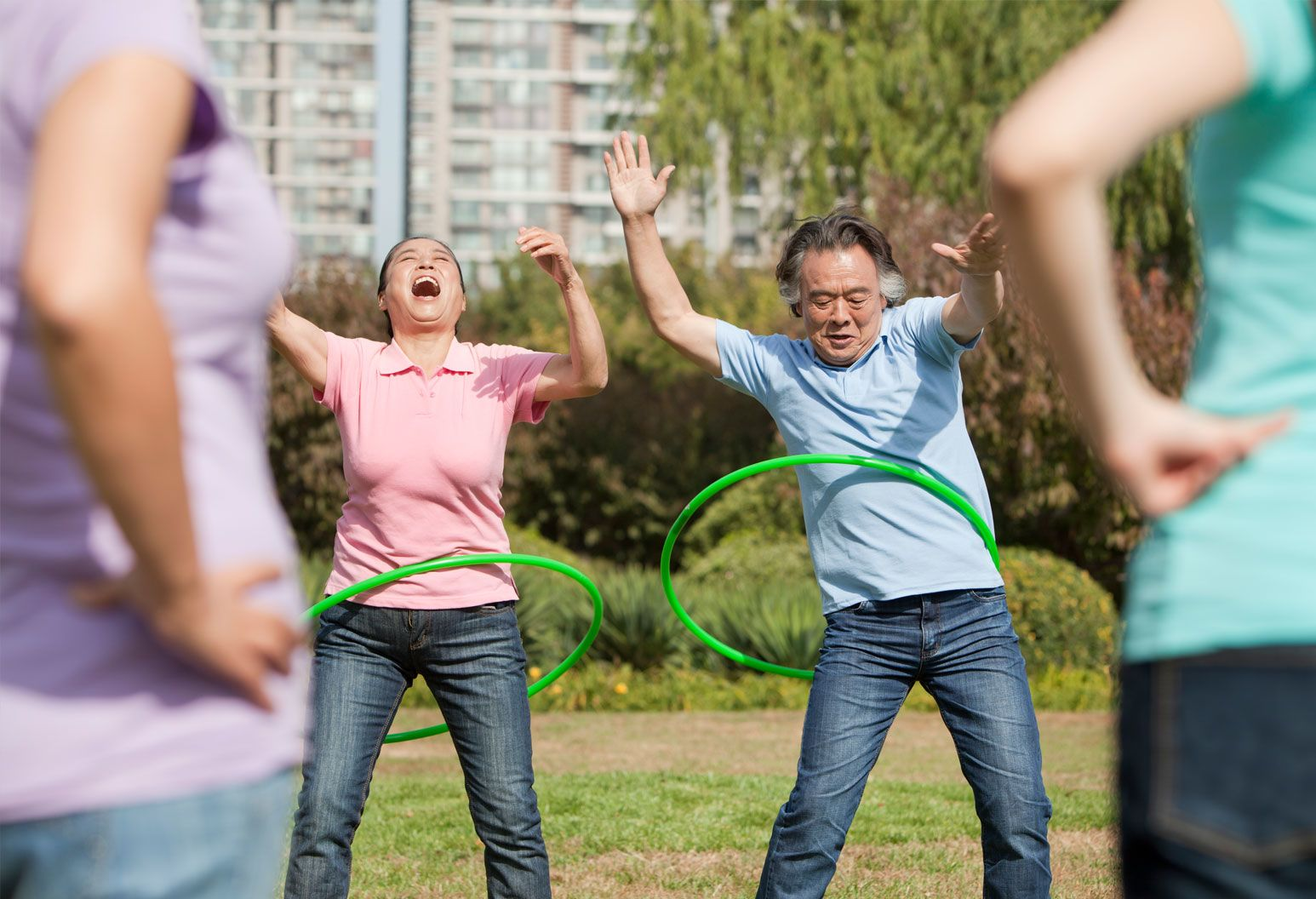 A man and woman are hoola-hooping in a field. They have their arms up and the woman's head is thrown back as she laughs. Two other people stand in the front of the frame with their hands on their hips.