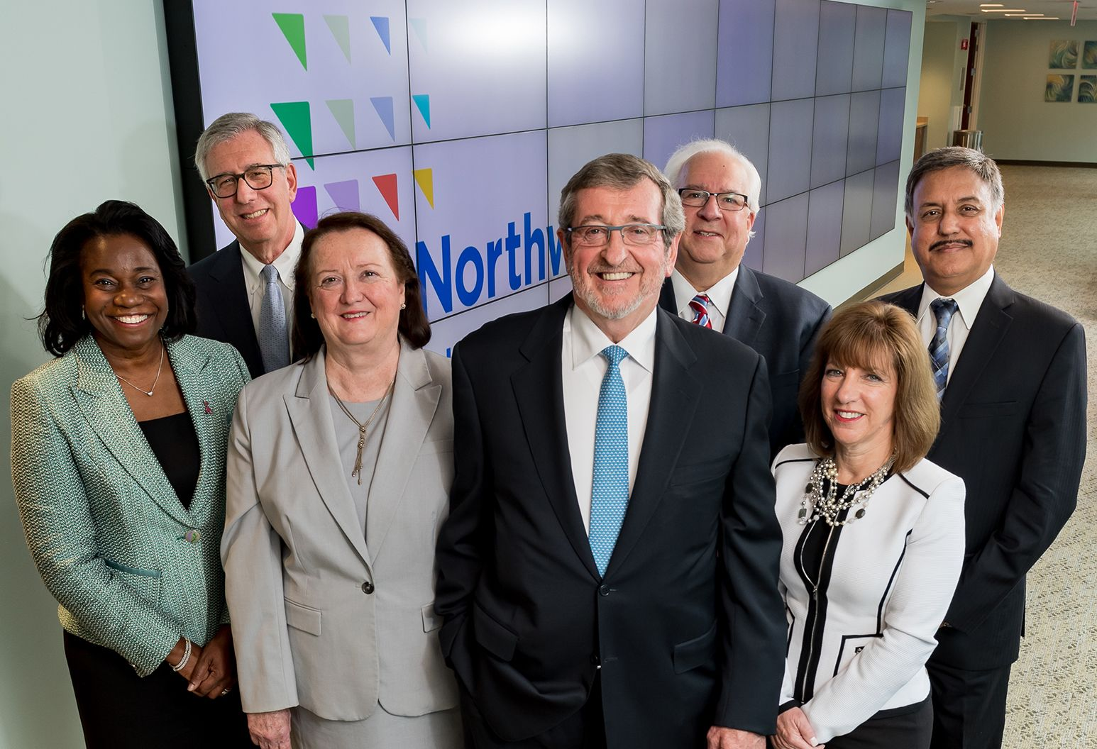 A group of Northwell Health senior leaders stand in front of a digital display that reads Northwell Health.