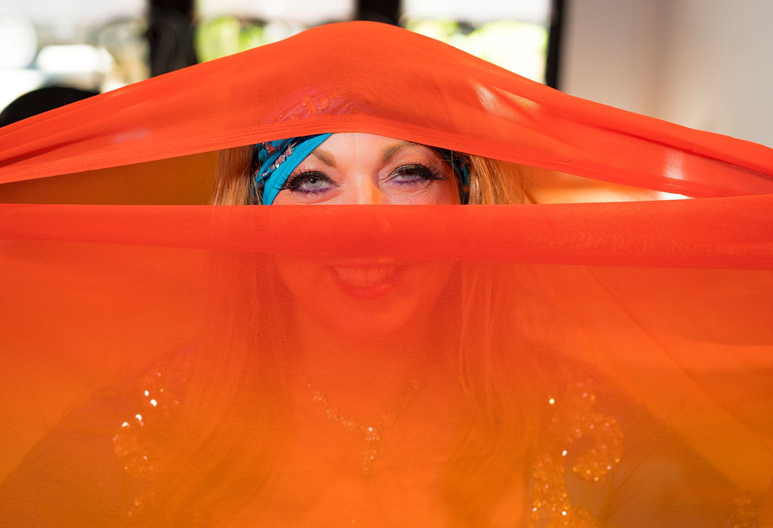Woman peeking through orange fabric