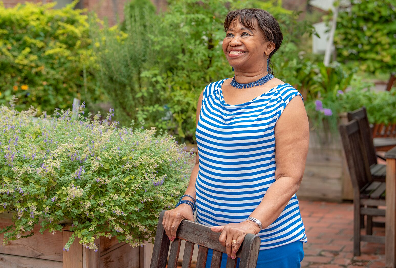 African American woman in blue and white striped top in a patio garden.
