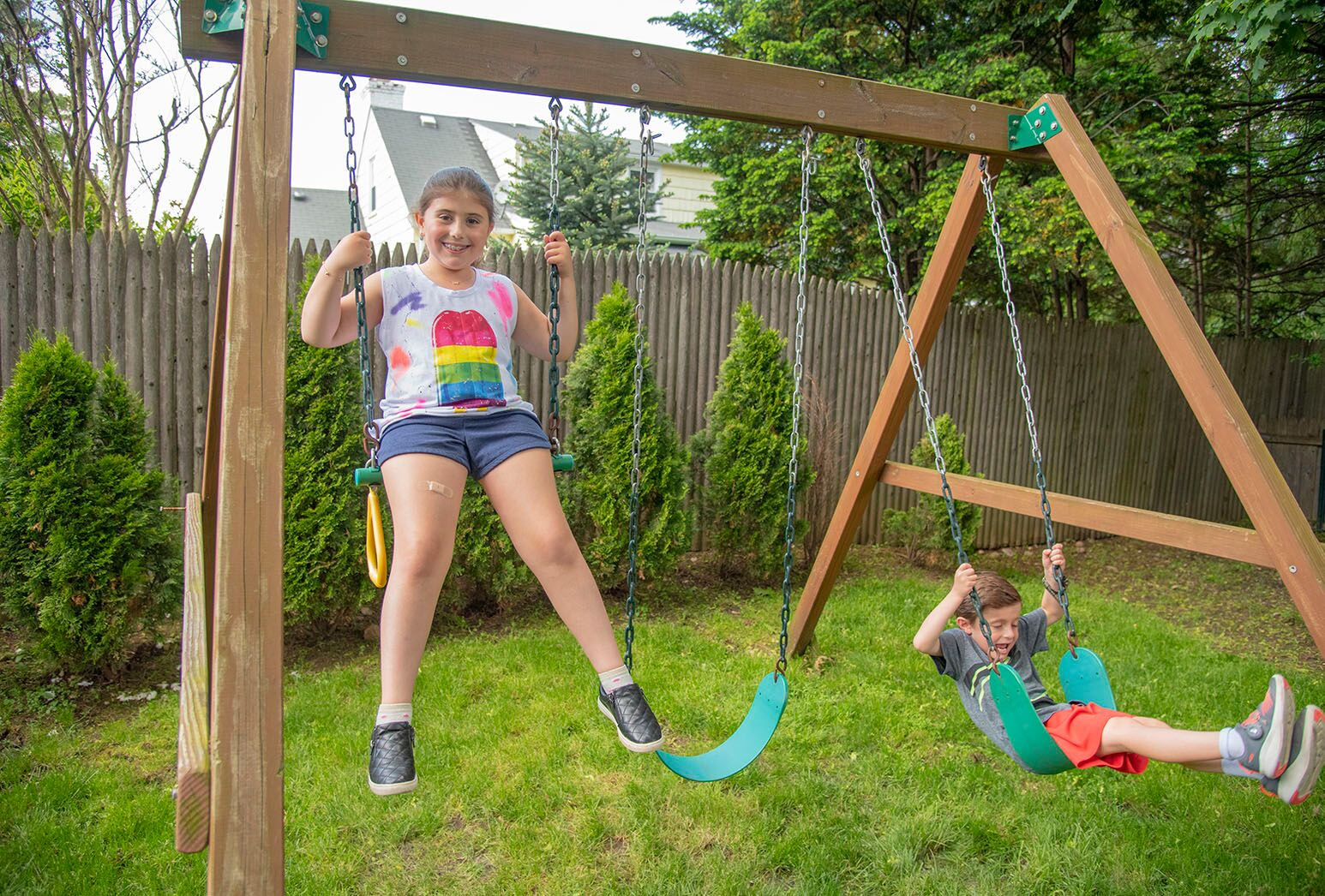 Young boy and girl swinging on a swing set in their backyard.