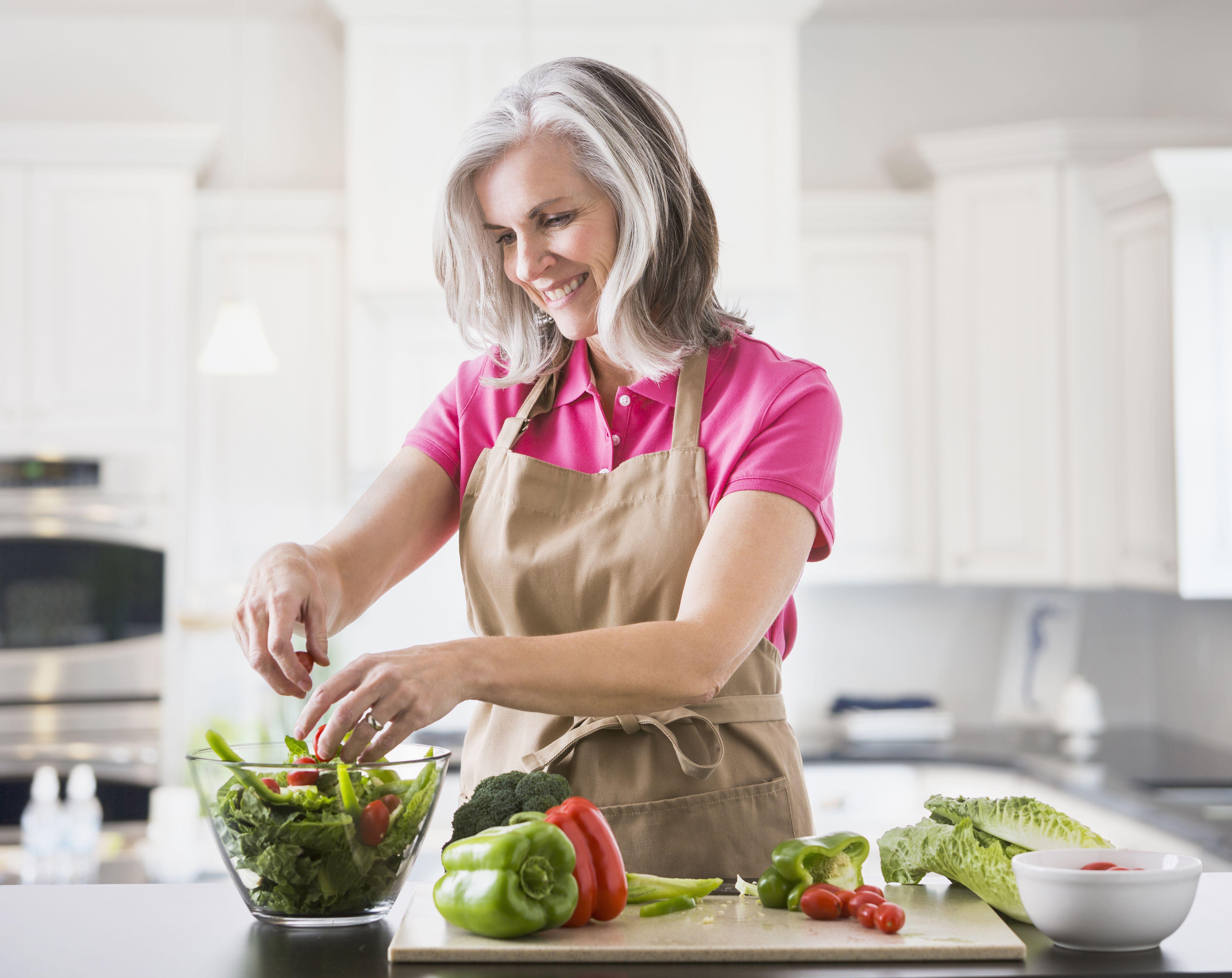 A woman prepares a salad.
