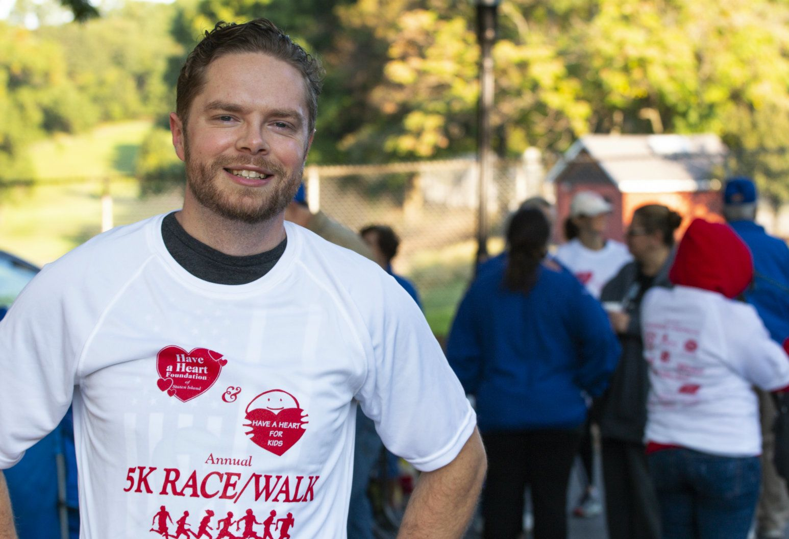 Michael Modica stands posing triumphantly after finishing a 5k race promoting heart health. The recipient of a heart transplant after an unexpected health issue, Modica has a new appreciation for his health and organ donors.