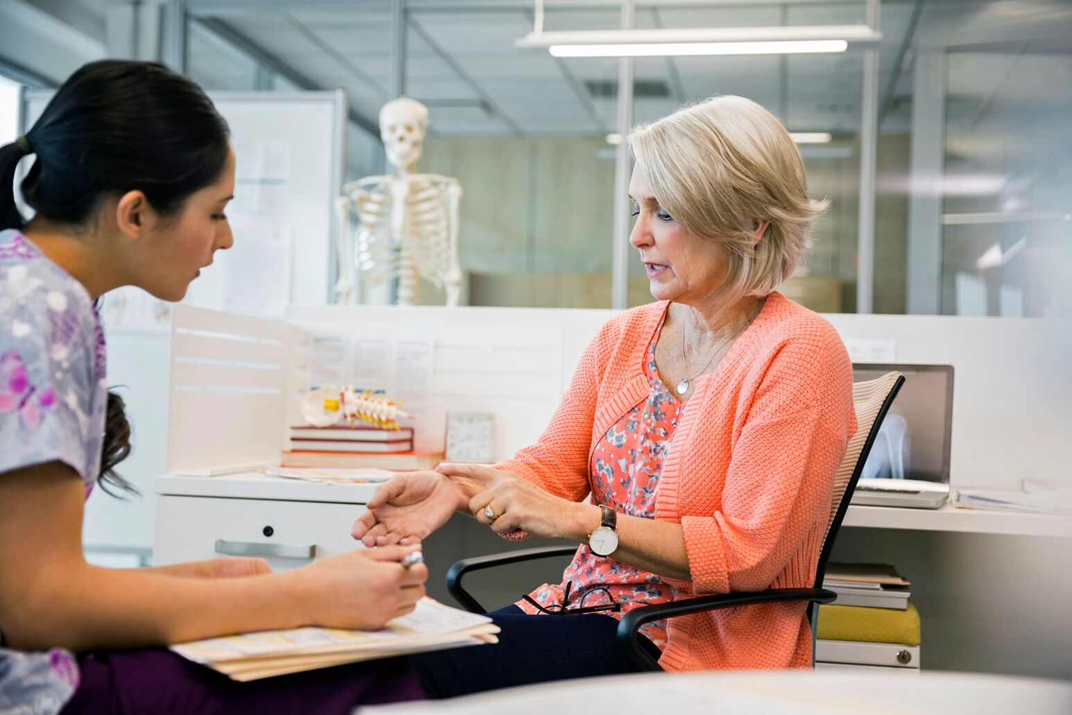 An elderly woman shows a female nurse her wrist pain. Ashley Burlage, MD, says that technology  is not the root of the musculoskeletal condition, but it can flare symptoms.