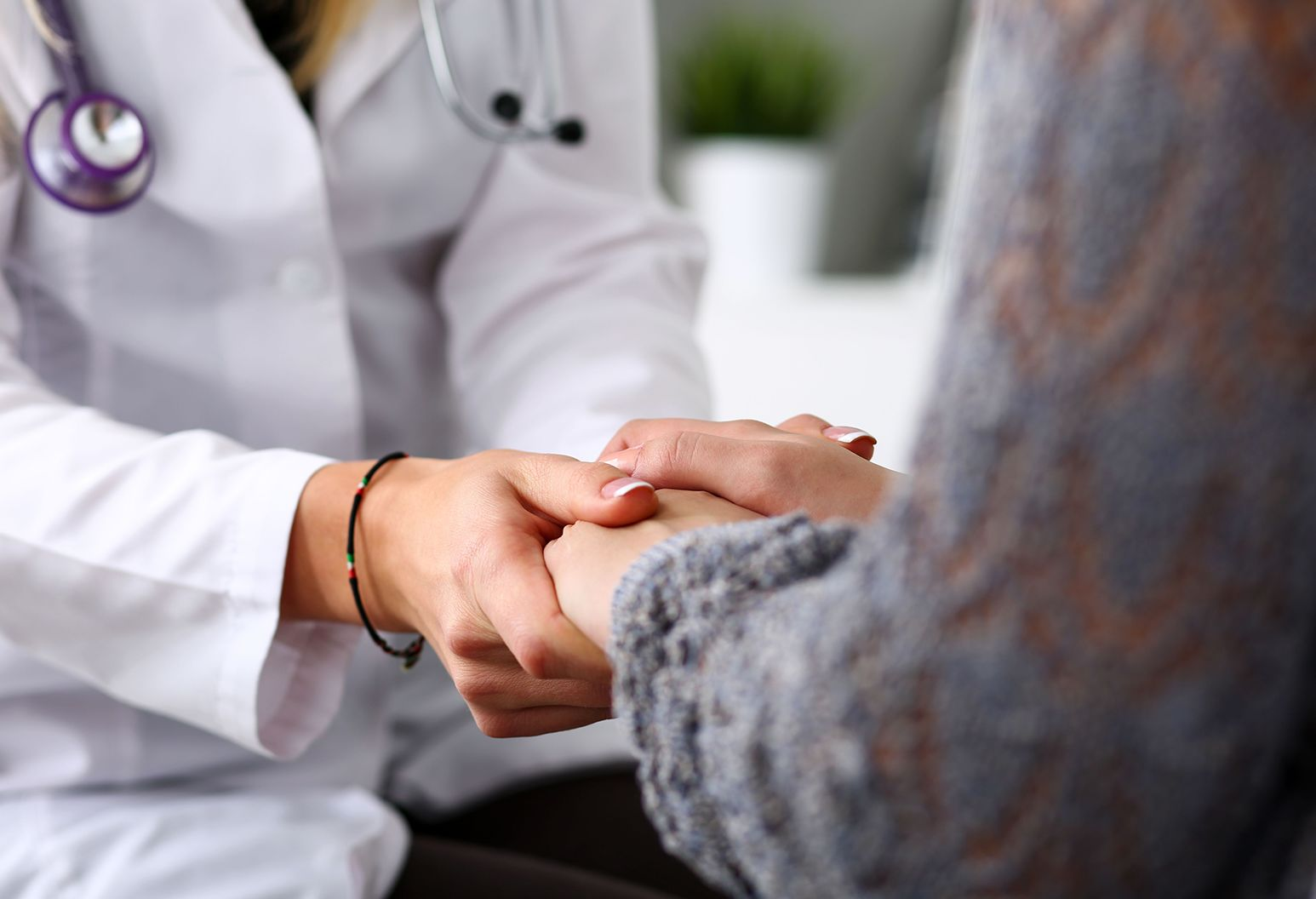 The hands of a woman wearing a white doctors coat is giving a comforting embrace to the hands of another person in a grey sweater.