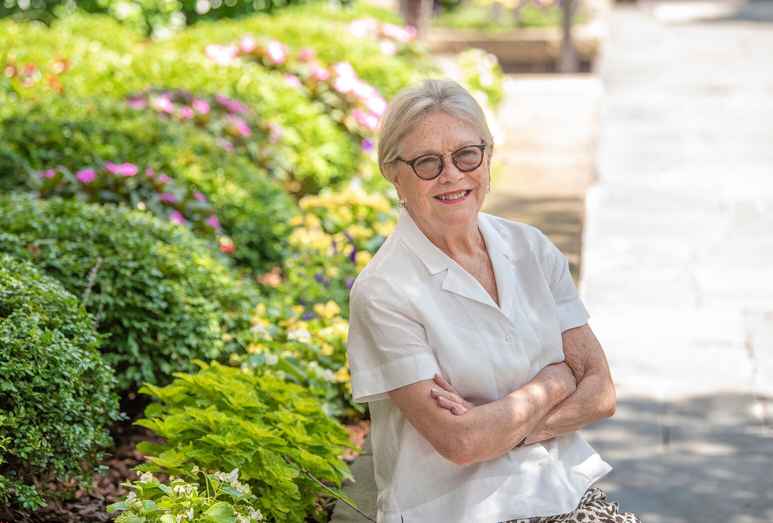 Woman in a white blouse and black-frame glasses in a garden.