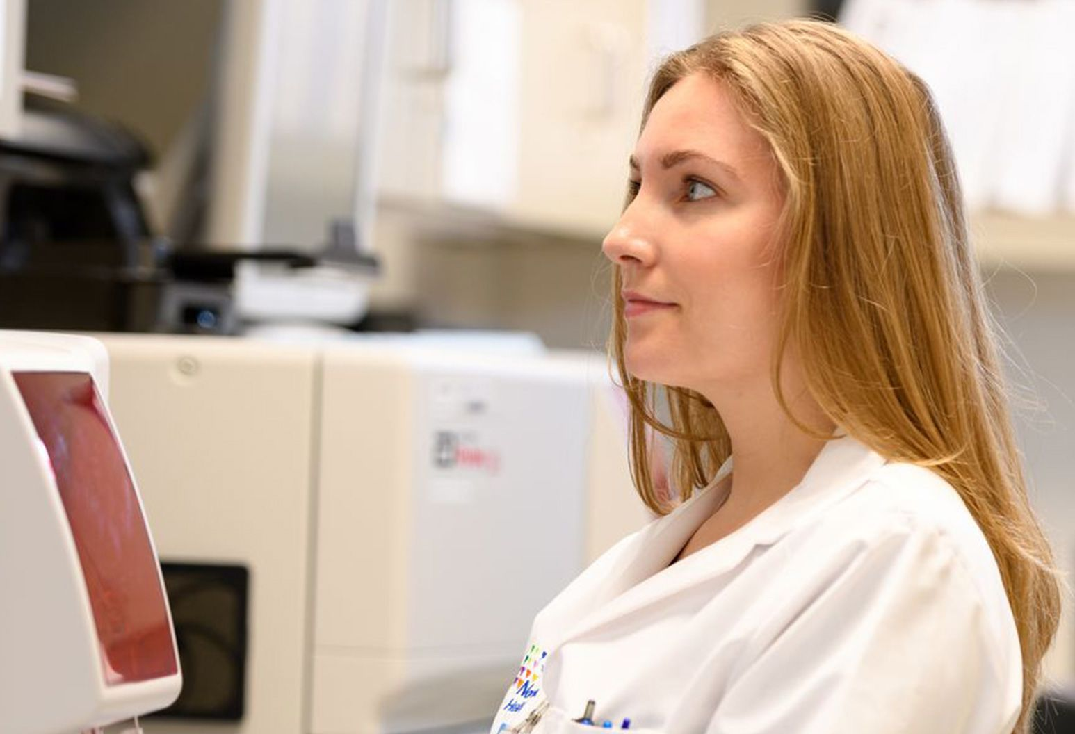 Female doctor wearing white lab coat is sitting at a desk in a research lab