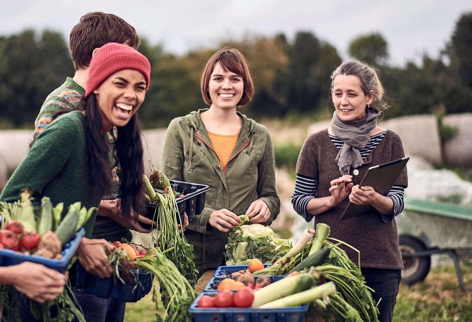 Group of community farming peers standing around picnic table in their shared allotment, laughing together whilst holding the freshly picked organic produce