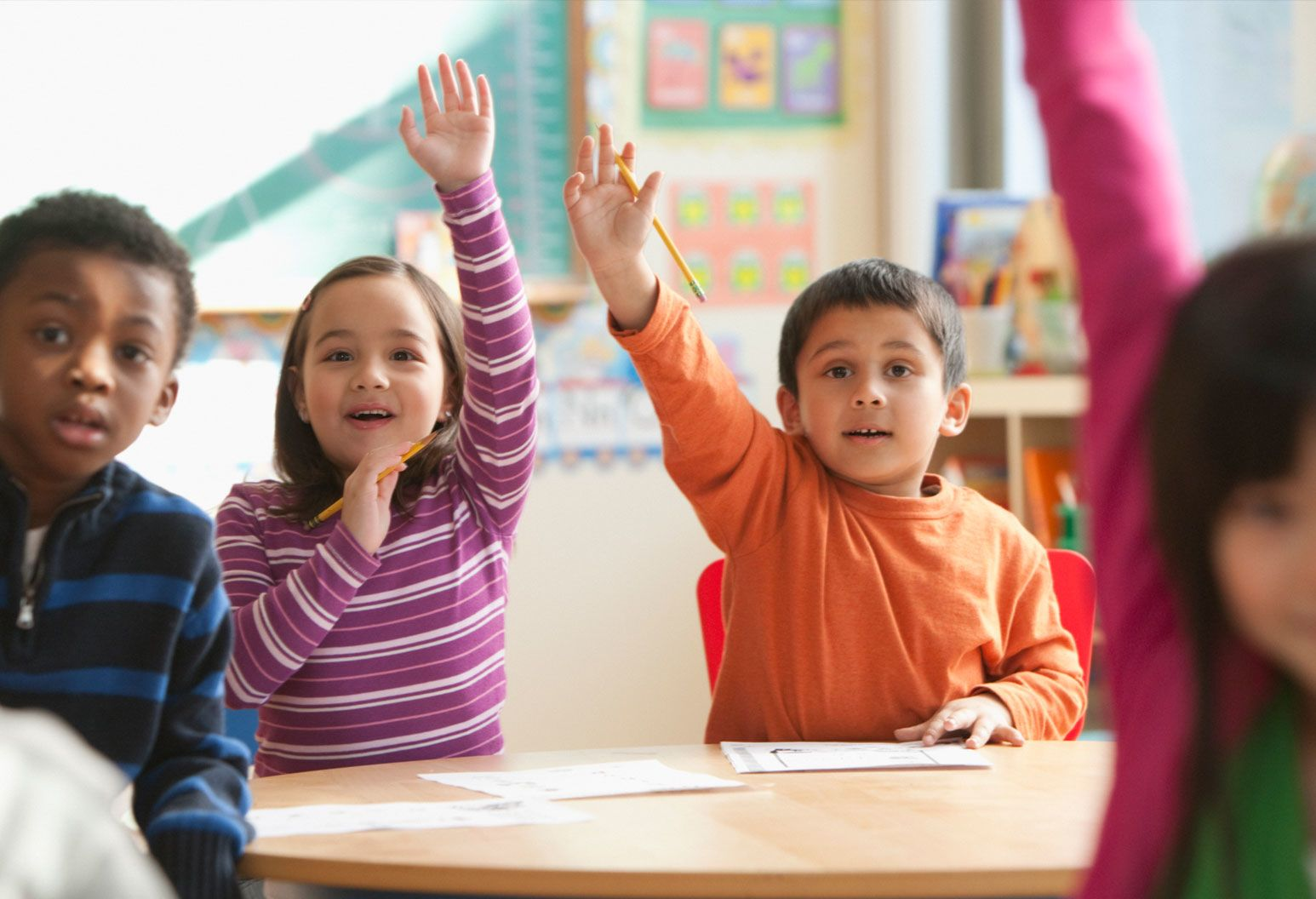 Classroom of young children, raising their hands, happily participating.