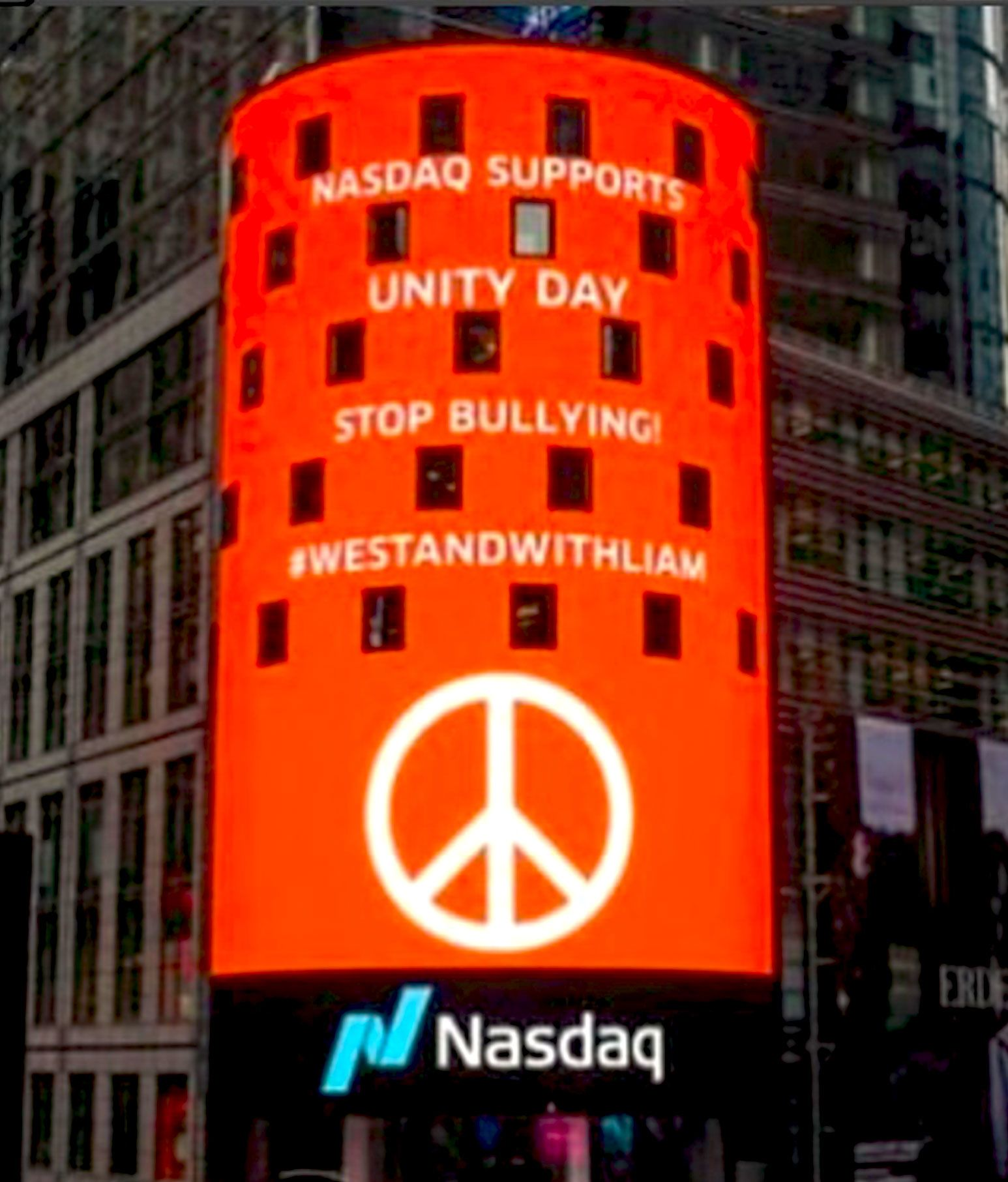 A large vertical led sign with a Nasdaq logo displays a peace symbol with the text #WeStandWithLiam