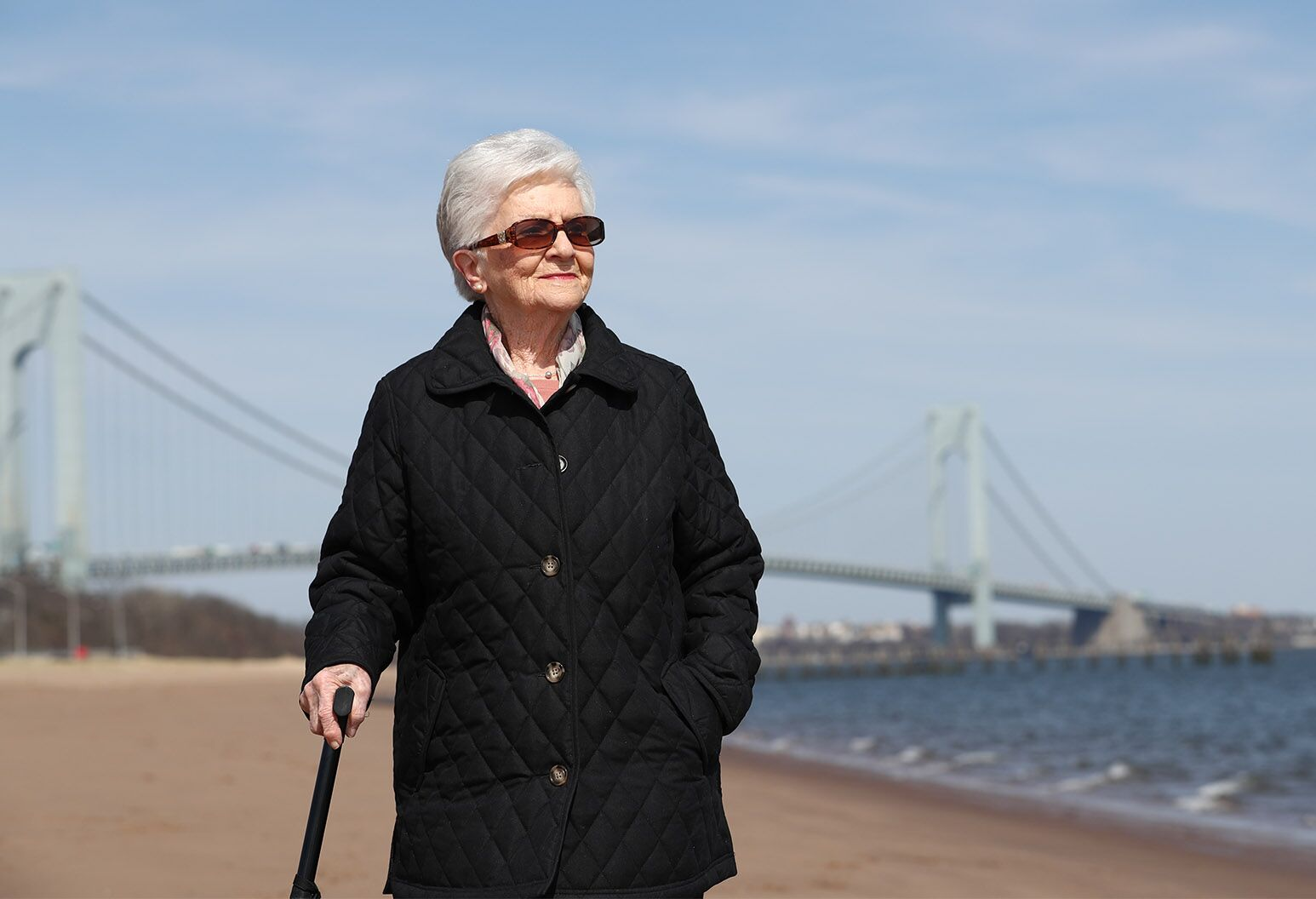 Woman in her 90s standing in front of a long suspension bridge.