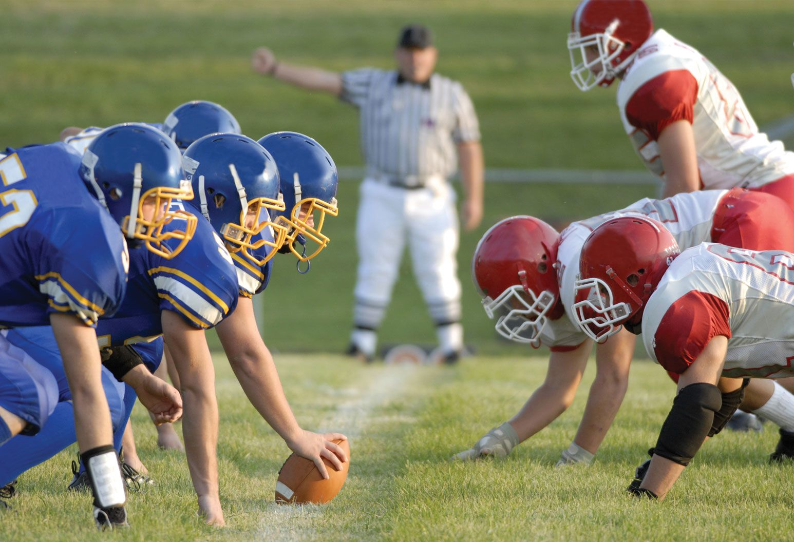Two football teams face each other, lined up to snap the ball. One team wears blue and gold uniform and the other wears red and white. A referee is in the background with his arm up.