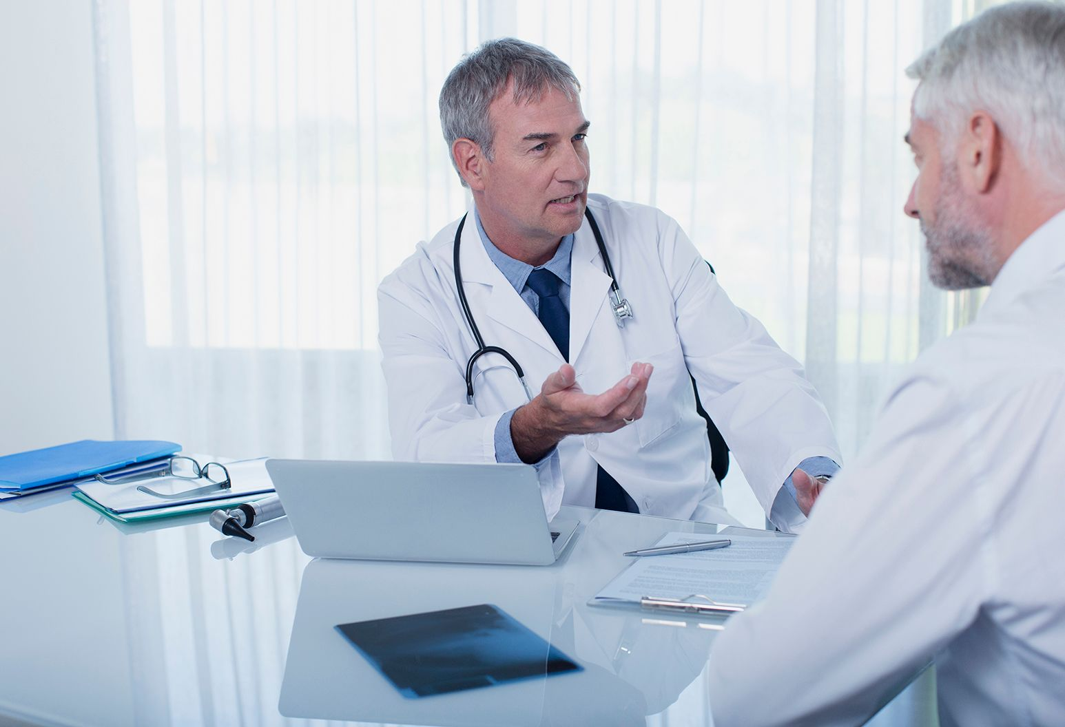 Male doctor wearing white lab coat sits at his desk while talking to a patient