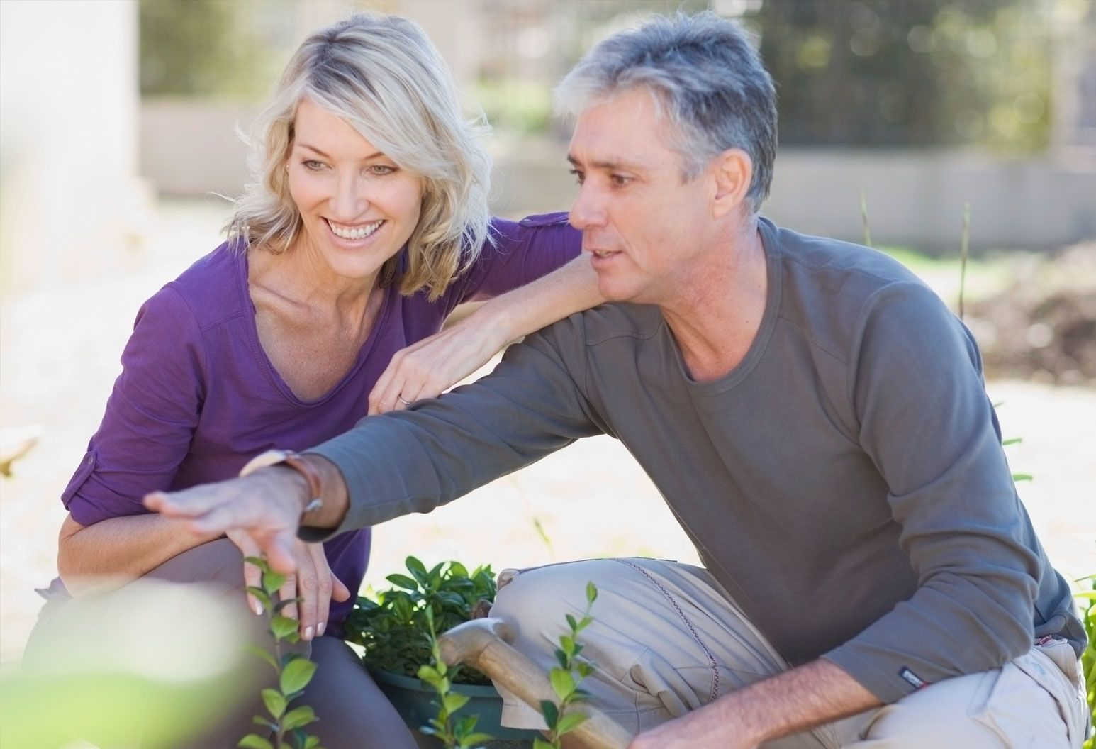 A middle-aged couple crouches down outside on a nice day, examining something out of focus with a smile on their faces.