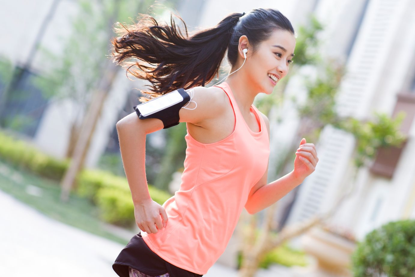 A 19 year old woman with black hair in a ponytail wears a peach tank top and has her phone strapped to her arm and earbuds in her ears. She is smiling as she runs outside.