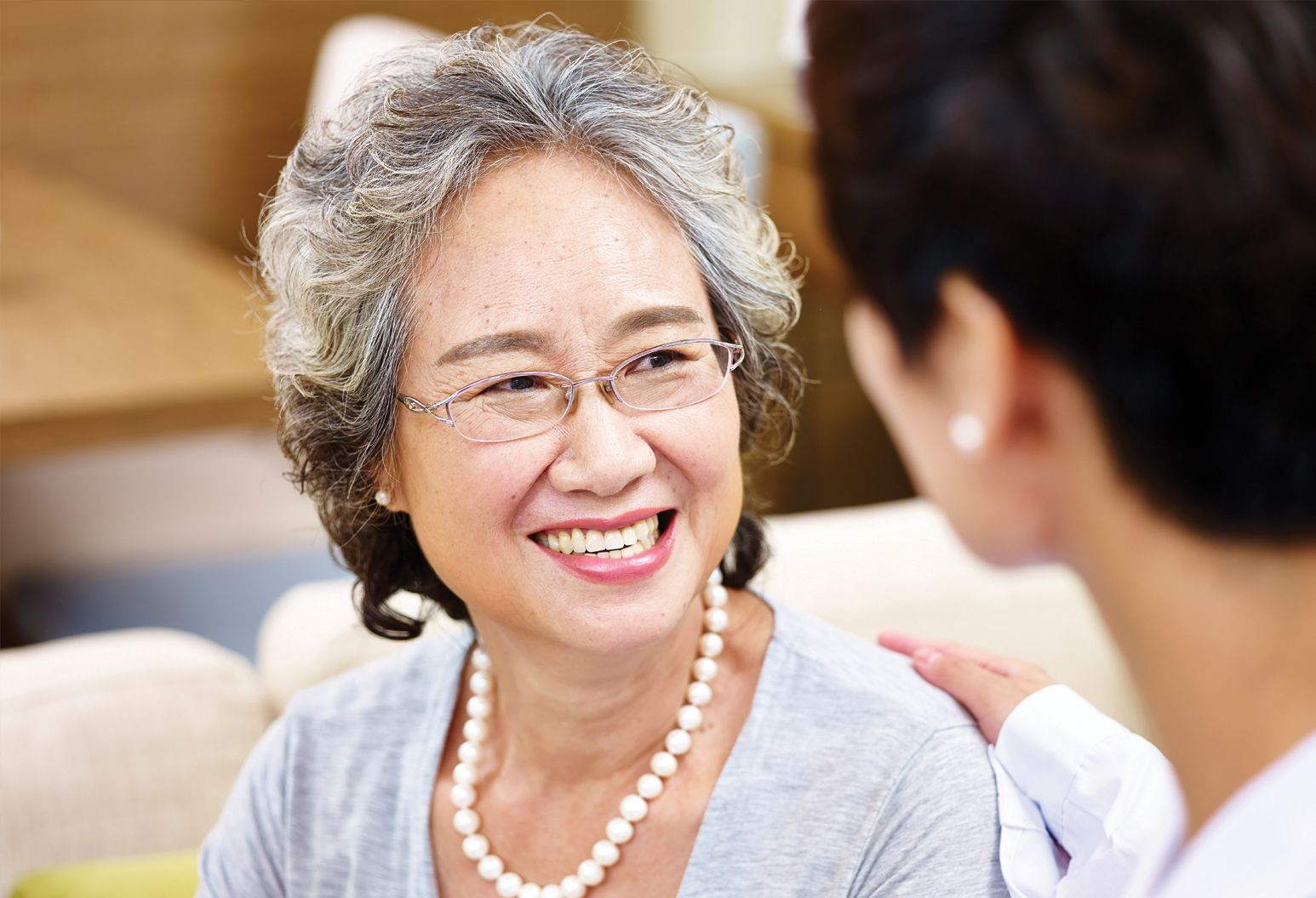 An elderly lady wearing glasses smiles as a hand is placed on her shoulder.