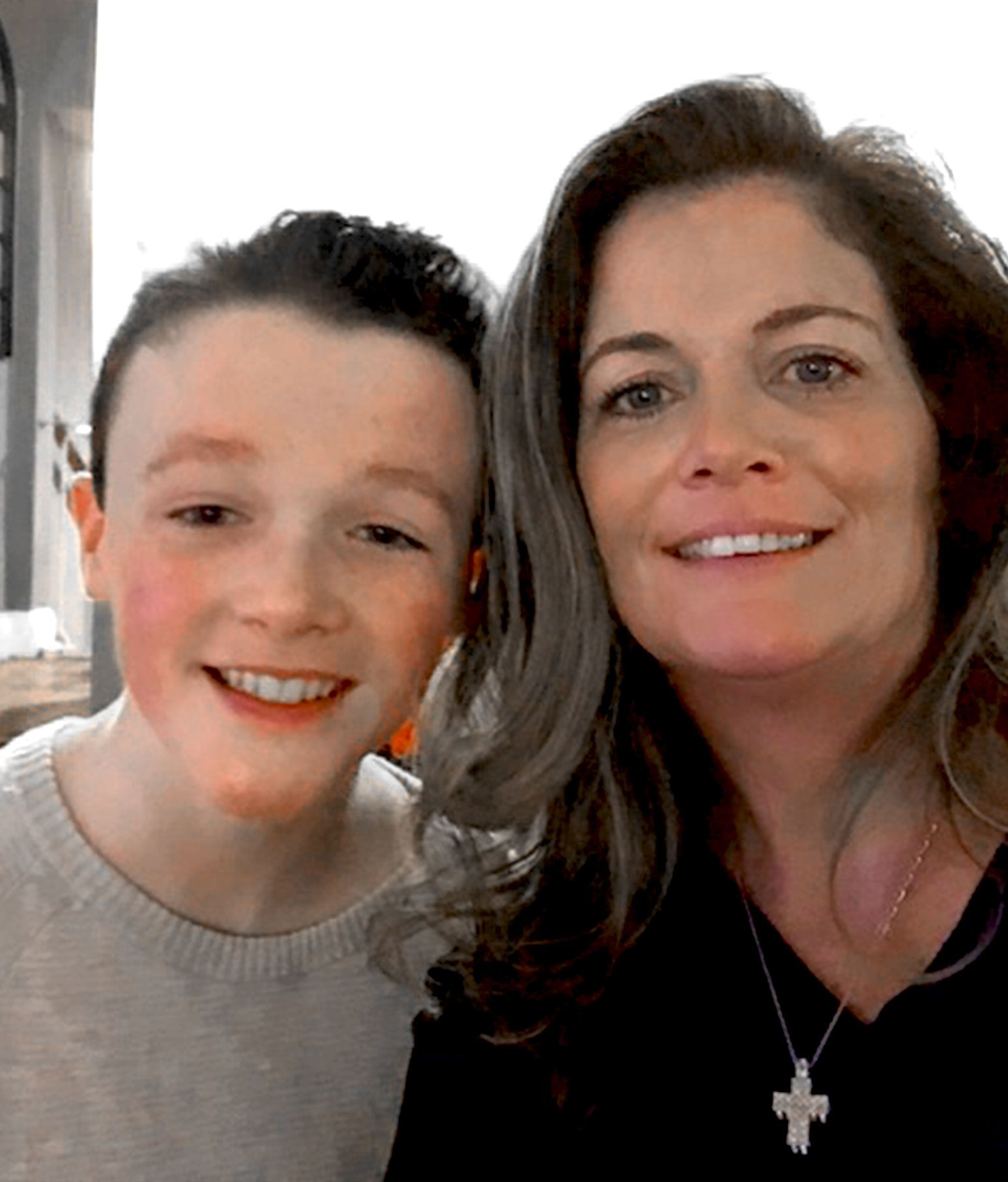 A woman in a black sweater and crucifix necklace takes a selfie with a young teen with a gray sweater and bright smile on.