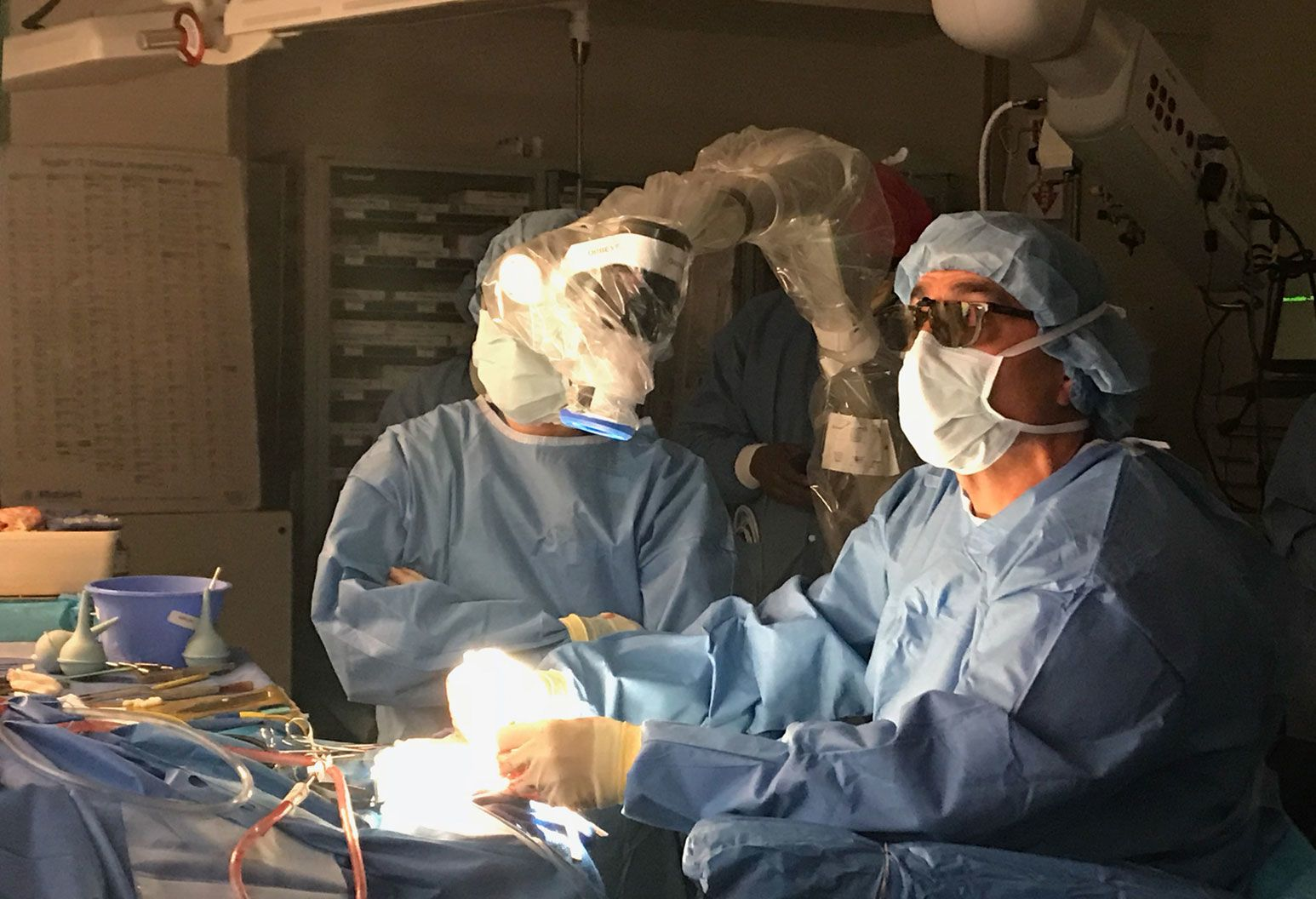 Group of surgeons in the operating room, wearing surgical gown, masks, and head coverings, are performing surgery