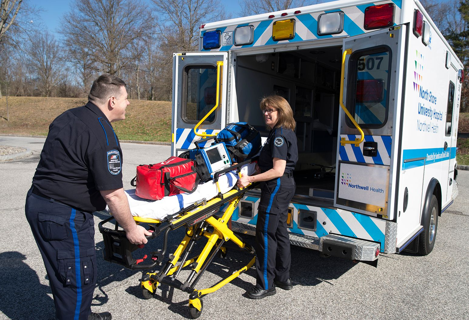 2 EMTs load a stretcher into the back of an ambulance.