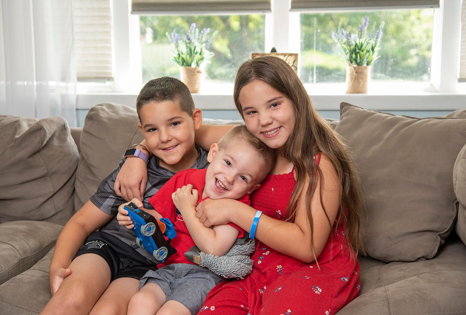 Two boys and a girl in a red dress with long hair, smiling and cuddling on a brown couch.