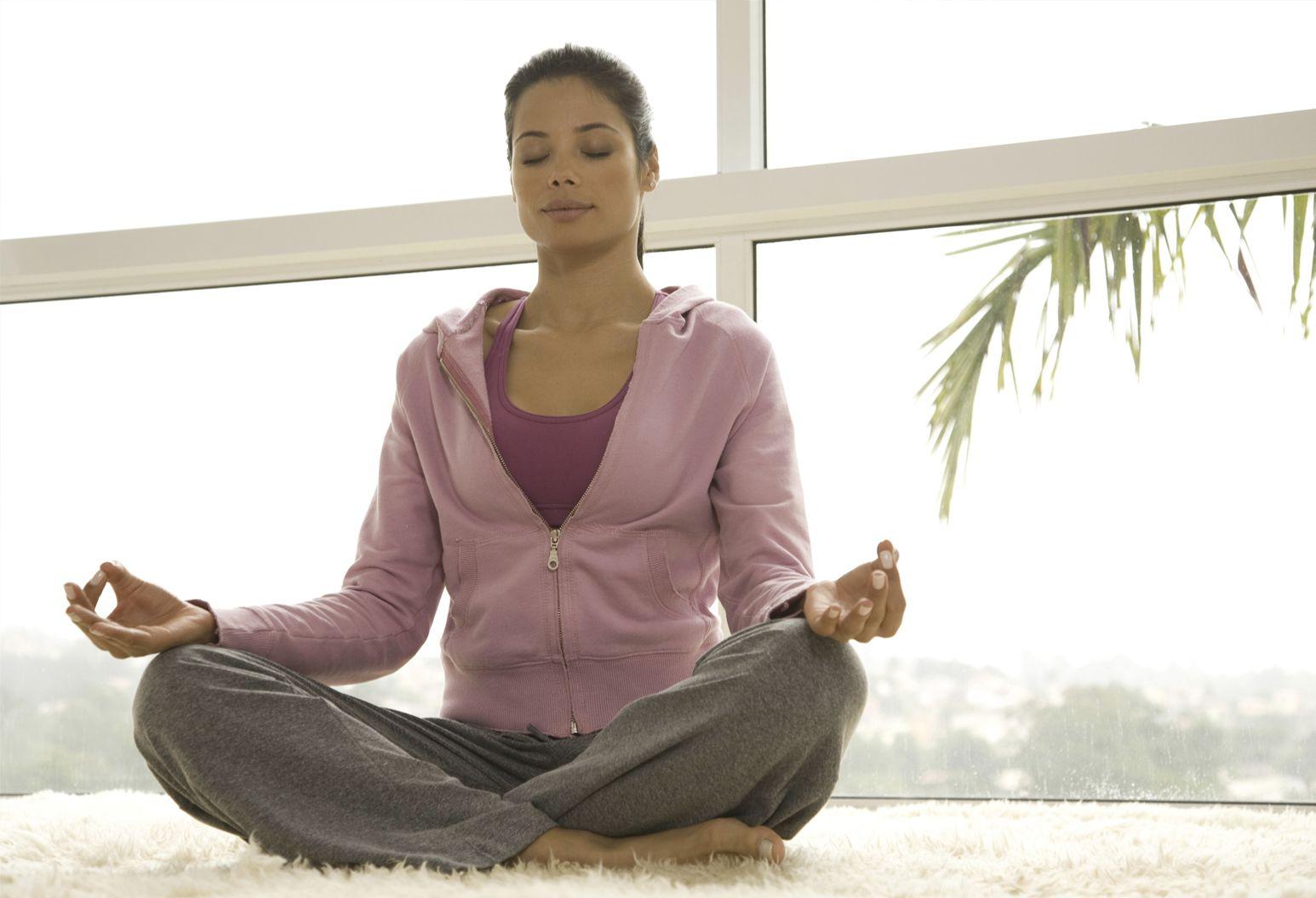 A women meditating in a cross legged pose.