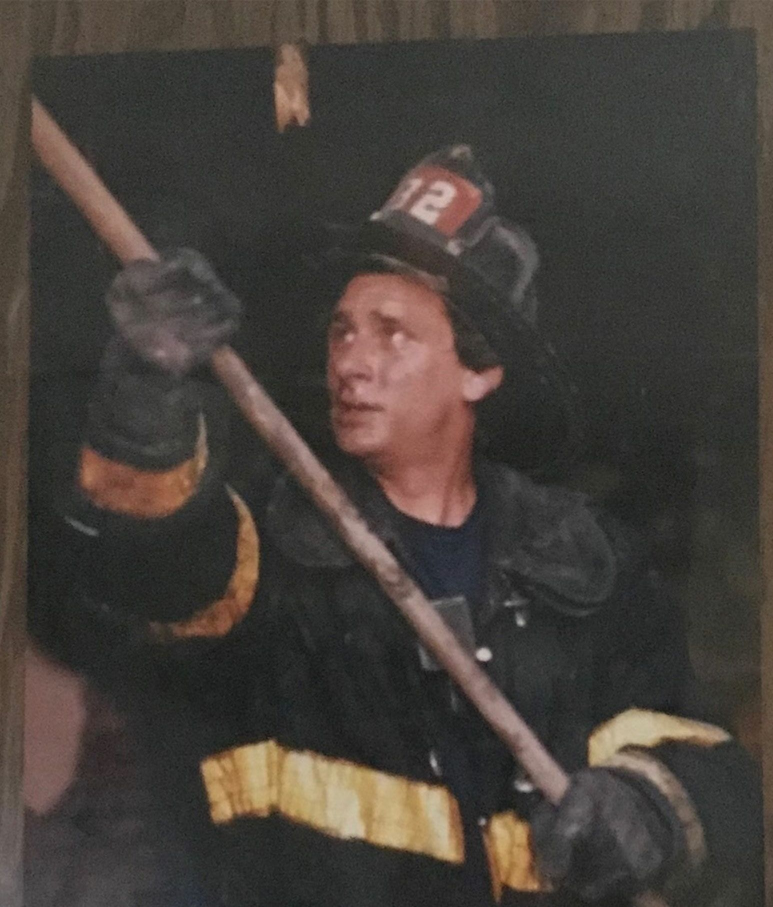 An aged photo of a fireman holding a pole against something not seen in the photo