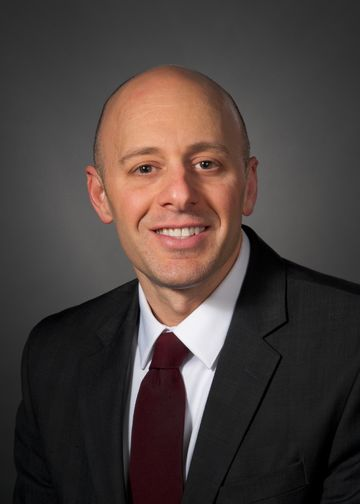 Michael Gitman, MD, wearing a dark suit with maroon tie