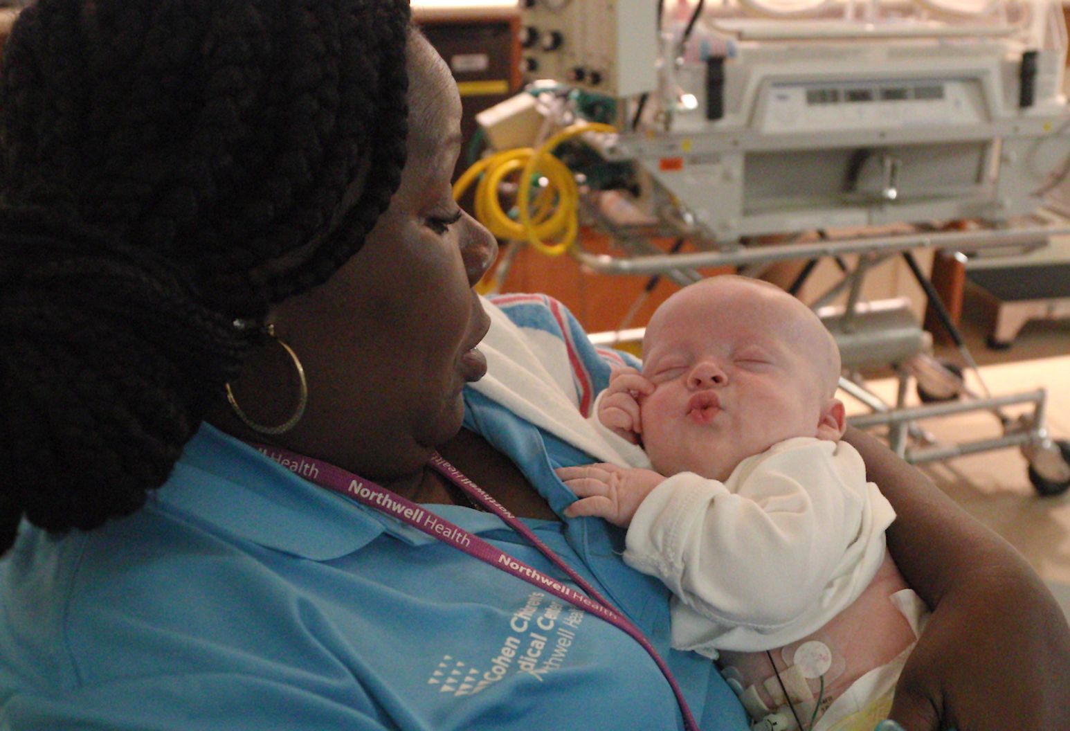 A nurse in a blue uniform holds a comfortably resting newborn baby to her chest.