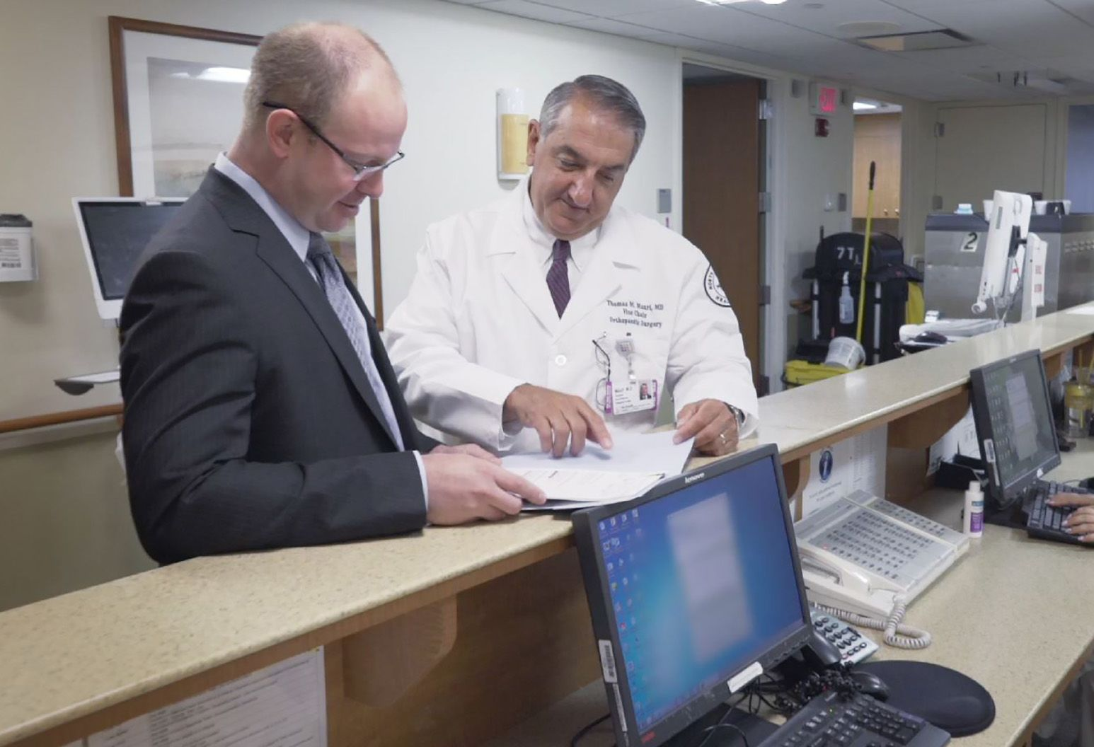A doctor wearing a white coat and a staff member wearing a suit stand at the front desk of a doctor's office and look at a patient chart together.