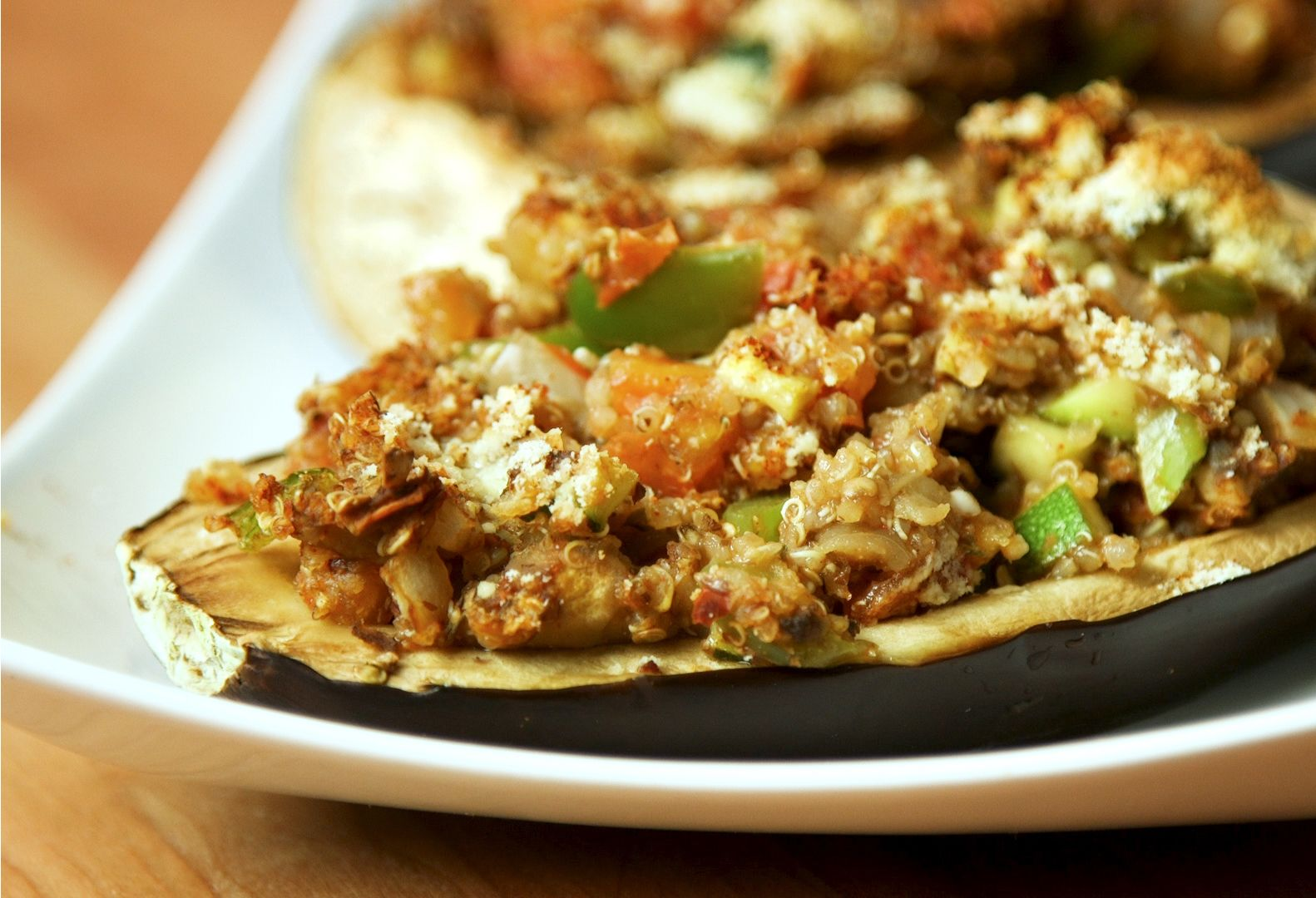 Close up picture of an eggplant shell filled with chopped vegetables and quinoa.