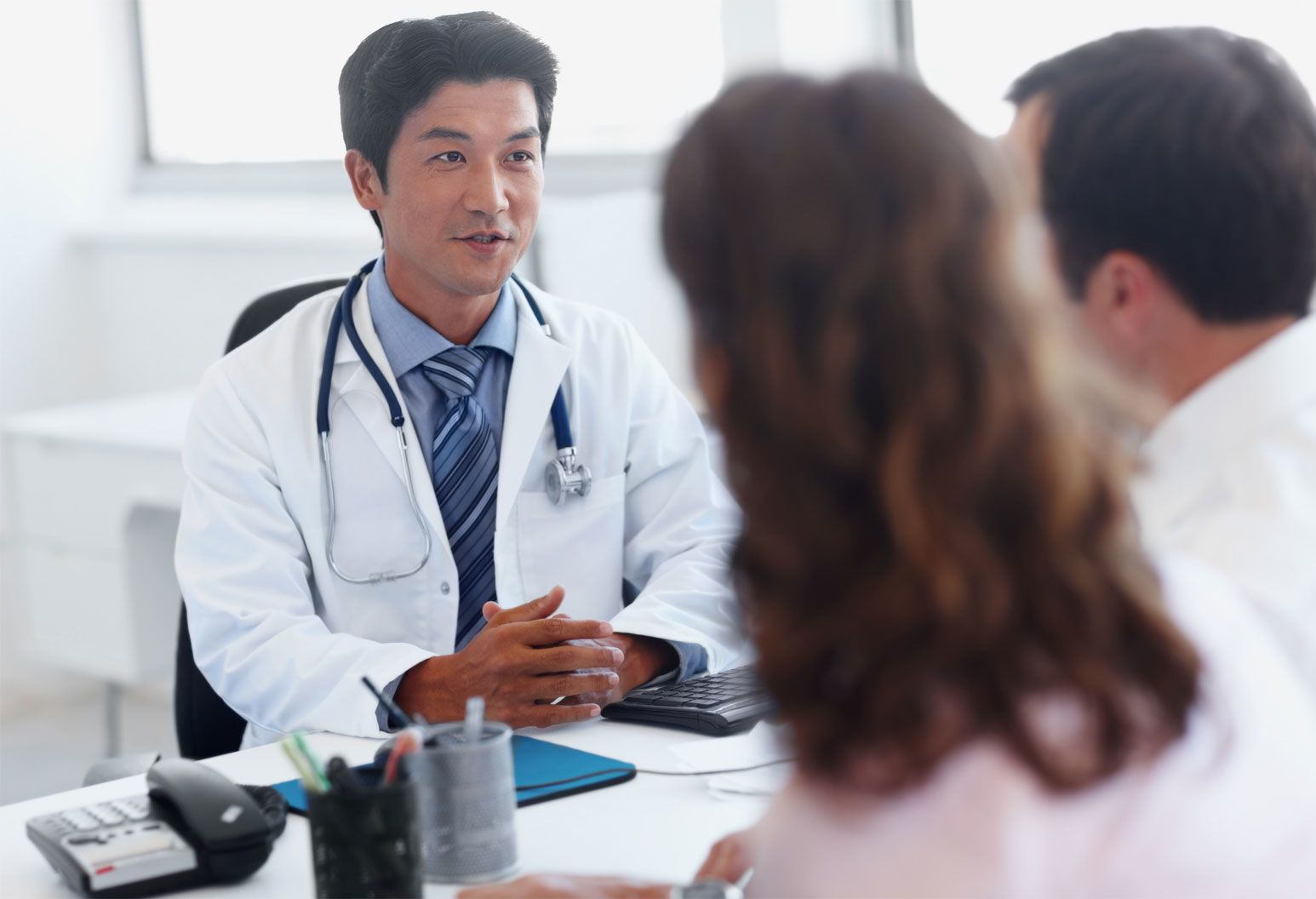 Male doctor sitting at desk wearing a white lab coat, speaking to male and female couple.