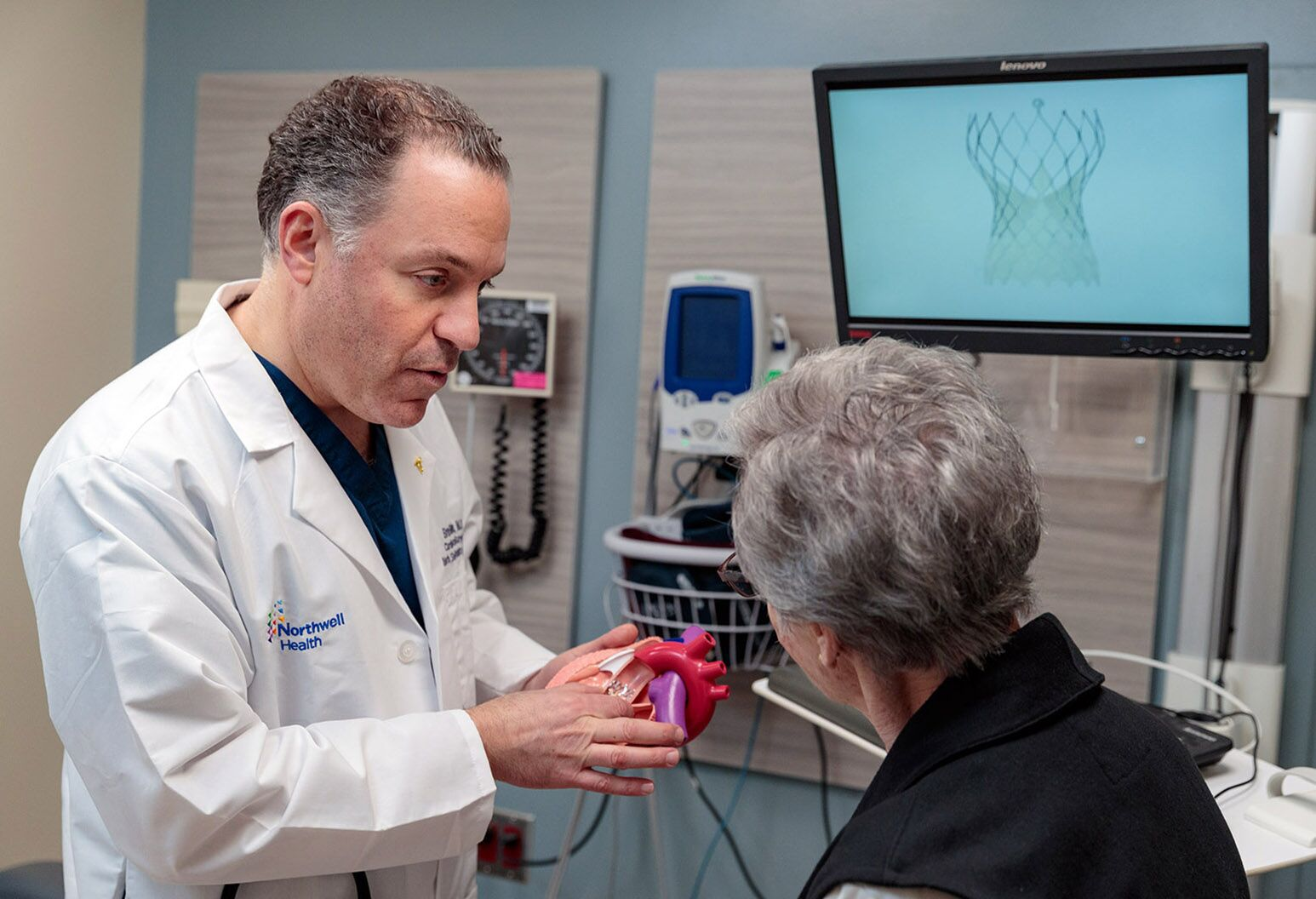 A doctor and patient pictured together, the doctor is holding a model of a heart.