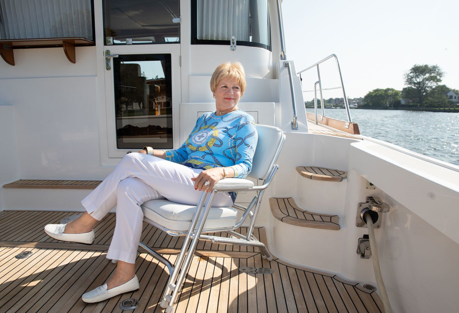 An elderly woman sits on on a chair from the deck of a private boat. She is wearing a nautical themed blue sweater and white pants. Smiling into the distance, she embraces the sunny day.