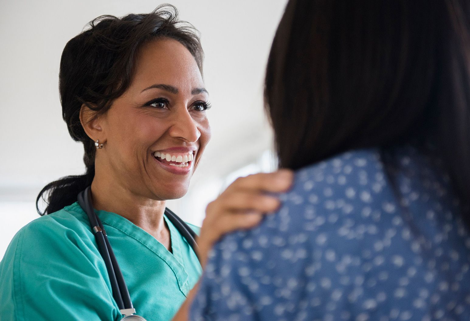 A doctor smiling while placing her hand on a patients shoulder.