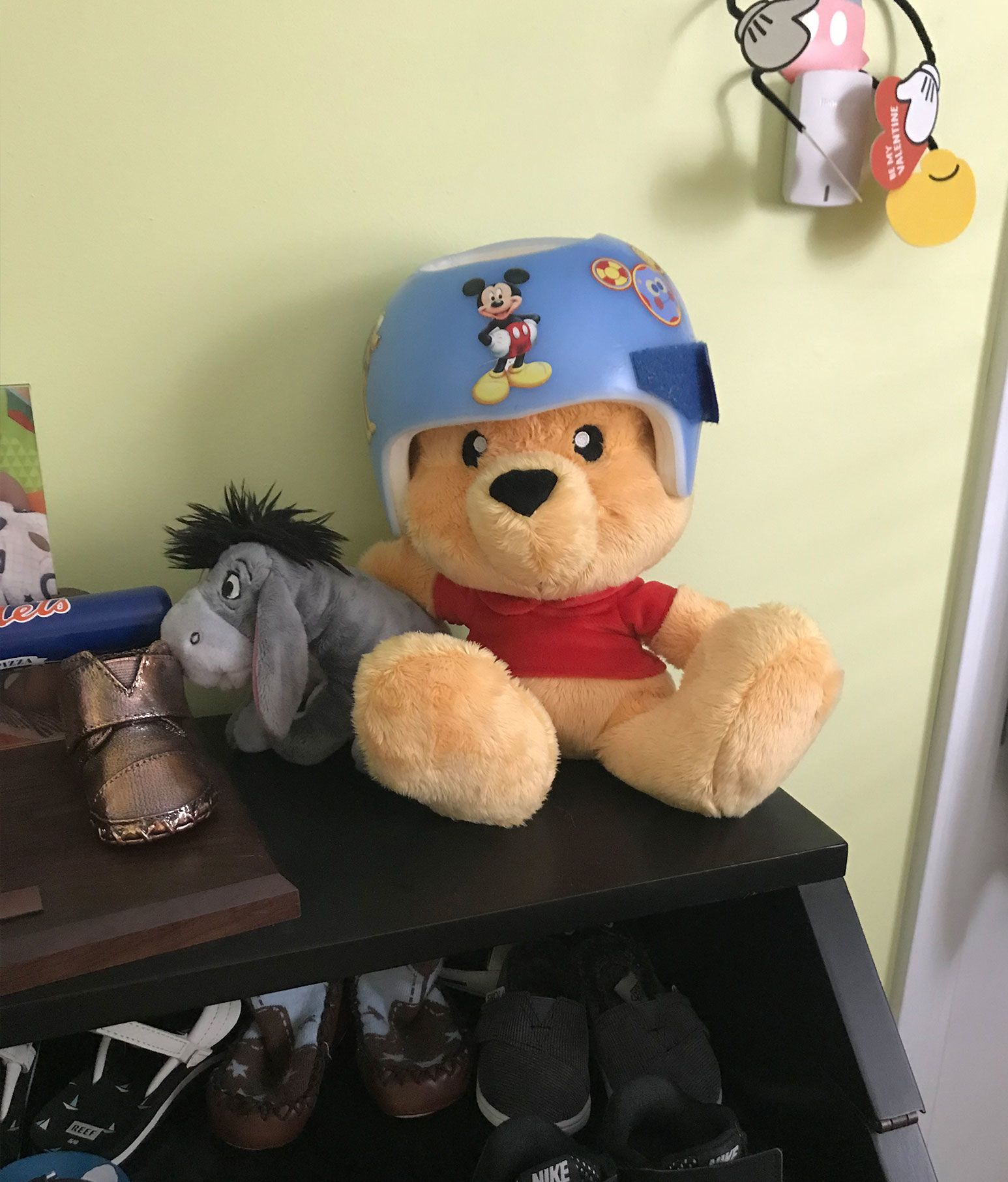 A Yellow stuffed bear rests next to a stuffed grey donkey on top of a shoe drawer. The yellow bear is wearing a blue helmet with stickers of Disney characters around it.