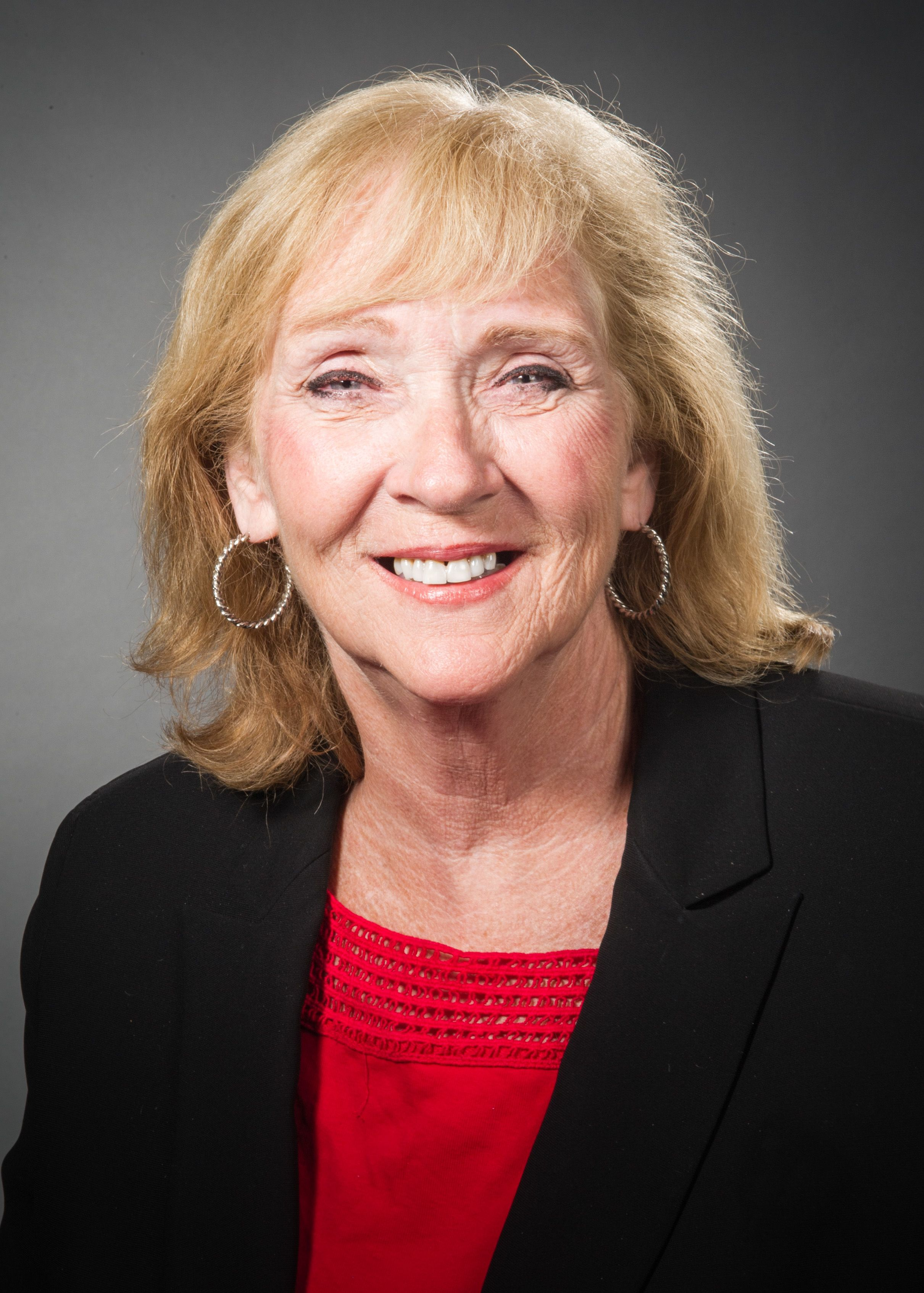 Barbara Geraghty, RN, in a black jacket and red blouse