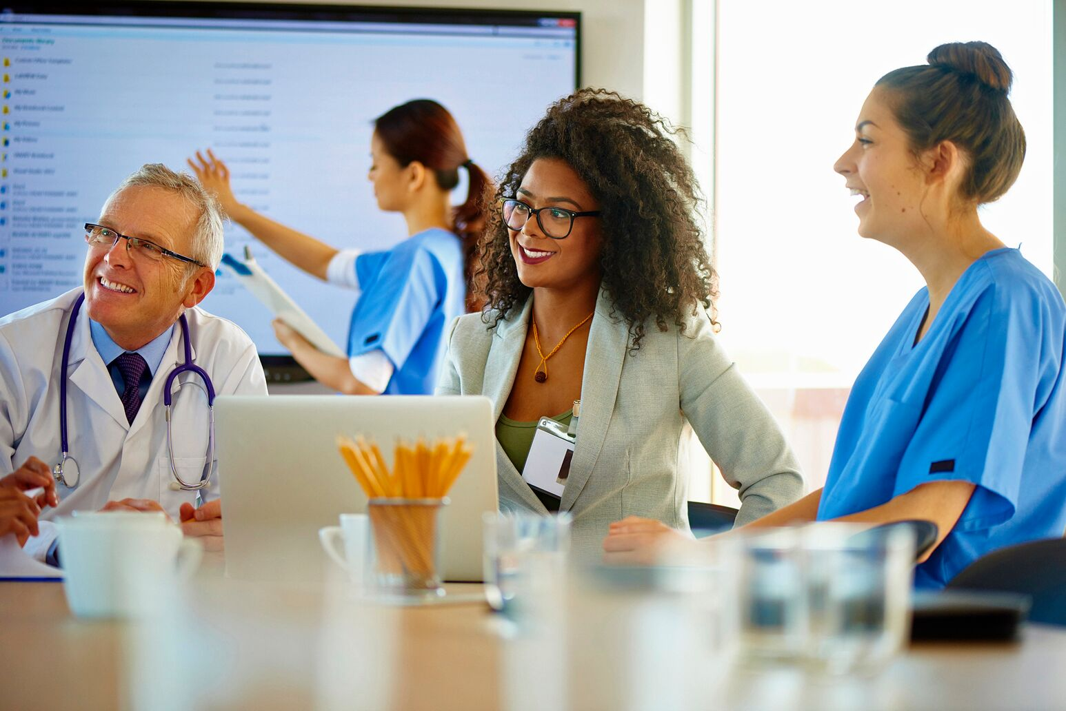 A female executive works with a team of clinicians. Michael Dowling says CEOs need to continuously invest in their employees to develop culture and familiarity with the organization.