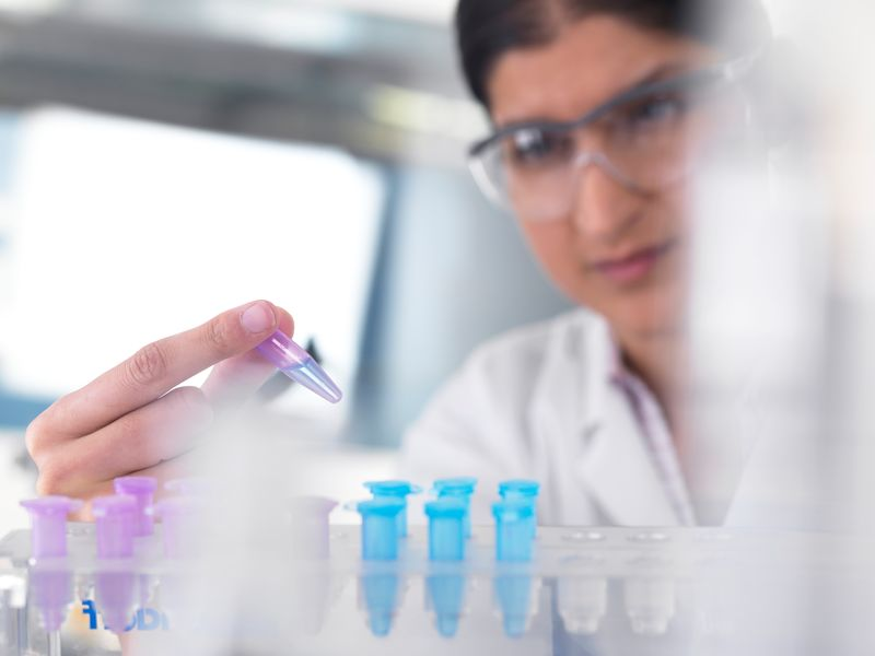 Researcher with protective glasses analyzing solution in a test tube